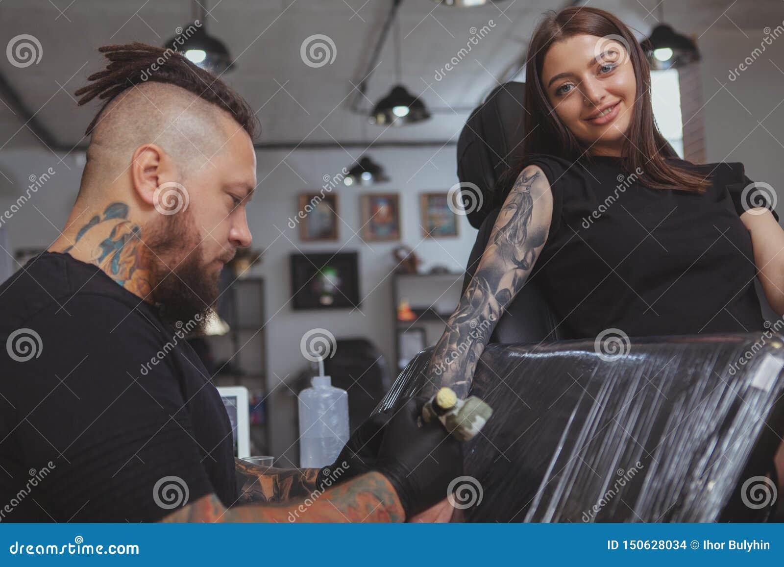 Jeune femme attirante obtenant le nouveau tatouage par le tatoueur professionnel