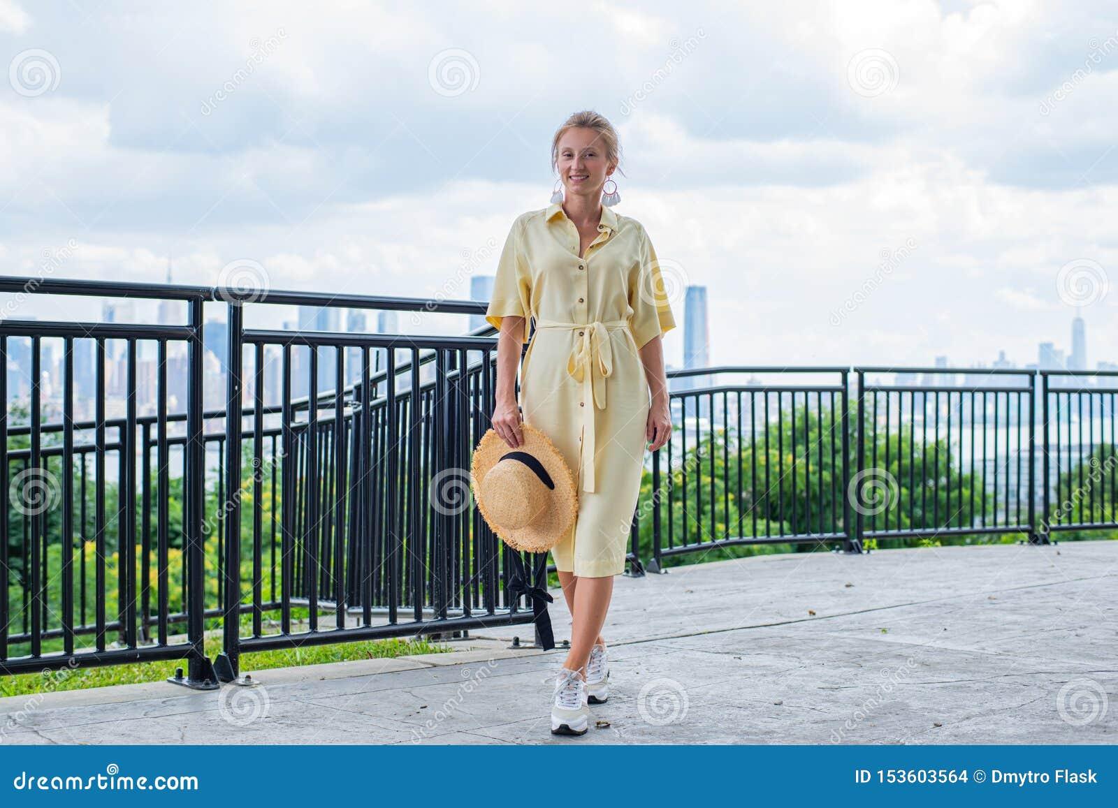 Jeune femme attirante regardant à la caméra et souriant sur le fond de New York City
