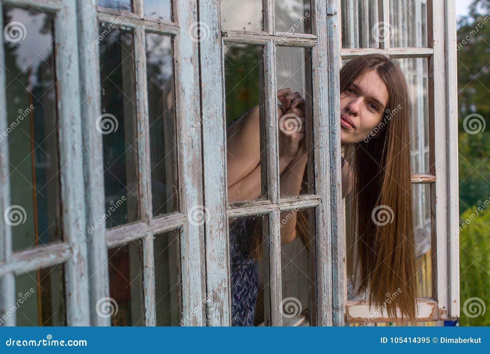 Jeune femme attirante s asseyant sur un rebord de fenêtre dans la maison de campagne