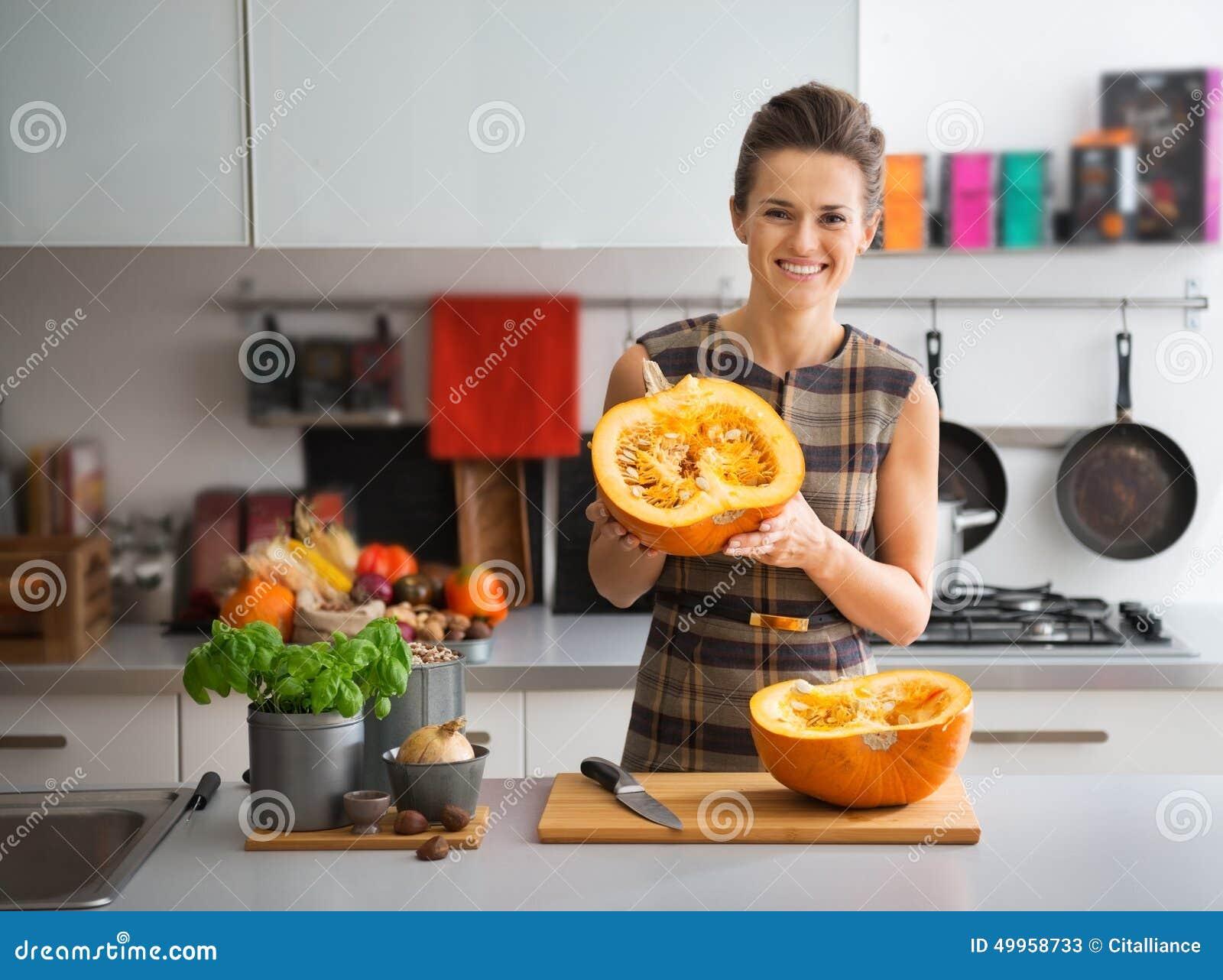 Jeune femme au foyer heureuse dans la cuisine montrant le potiron
