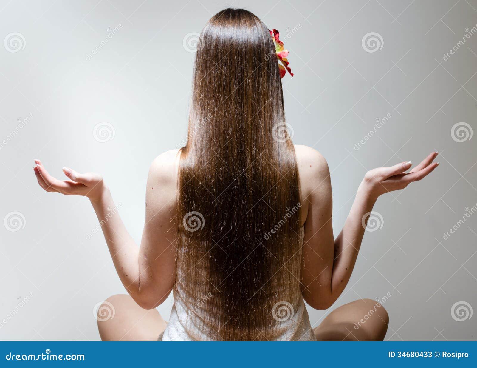 Jeune femme avec de longs beaux cheveux se reposant dans la pose de yoga