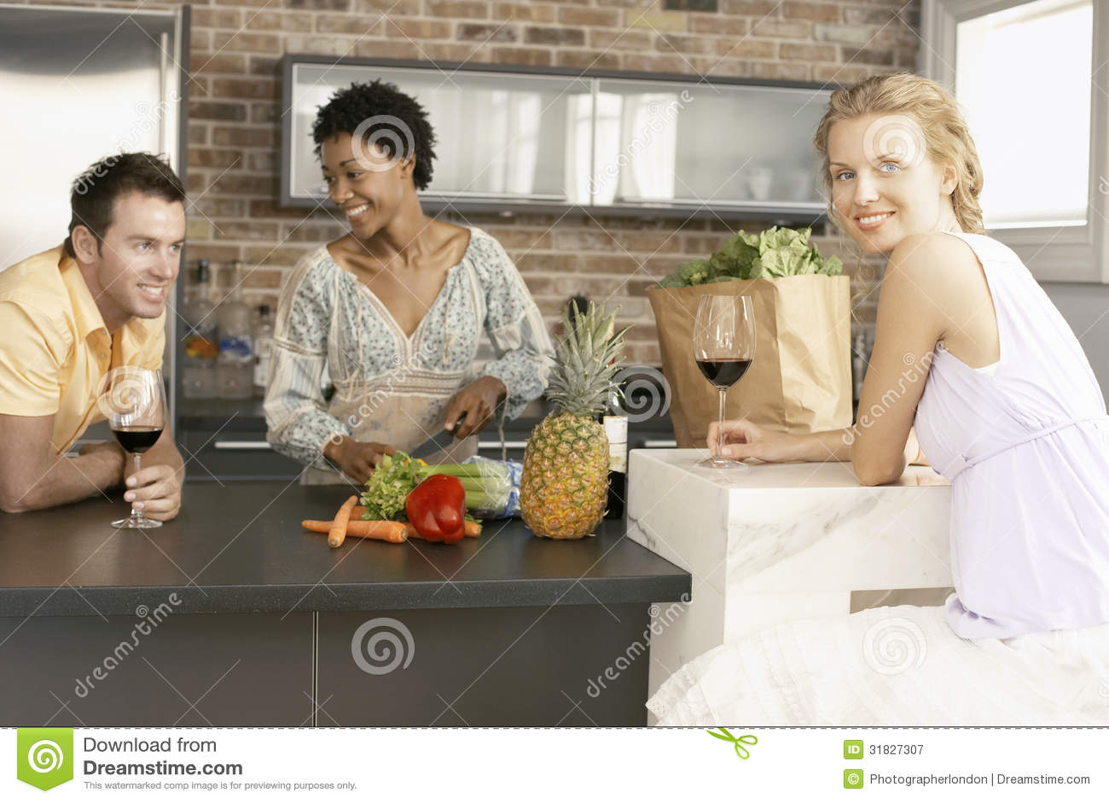 Jeune femme avec des amis préparant la nourriture dans la cuisine