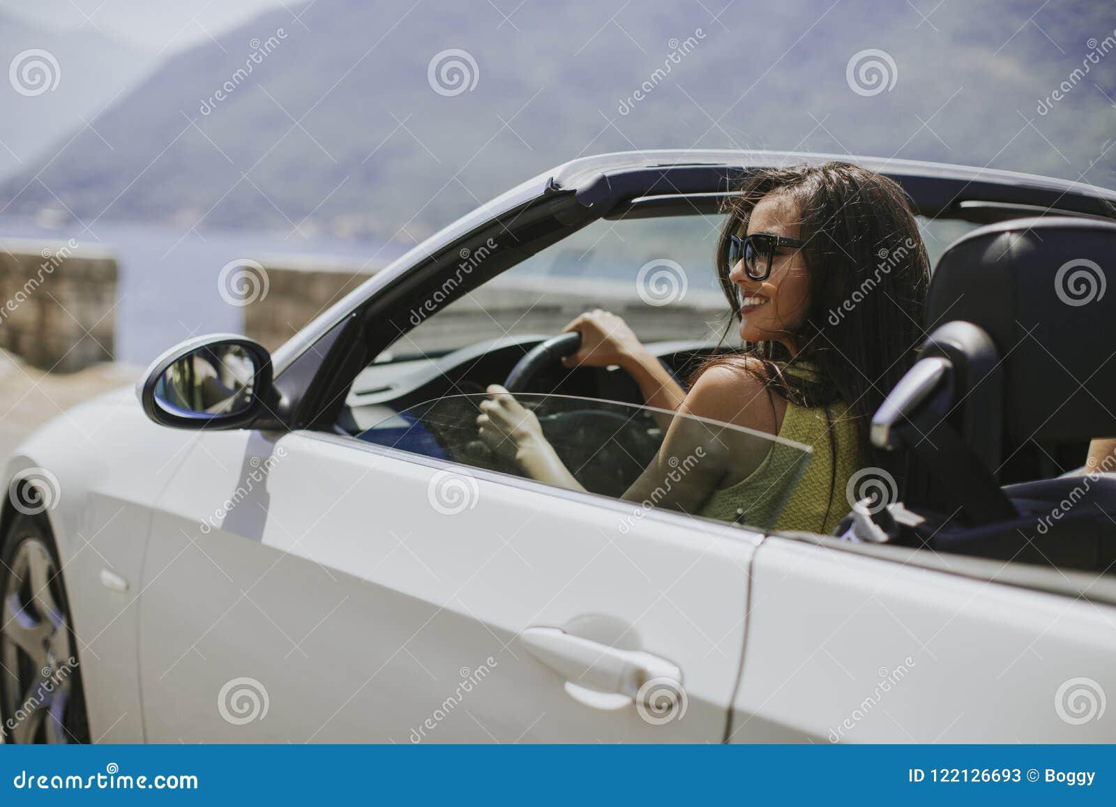 Jeune femme avec des lunettes de soleil conduisant son automobi supérieur convertible