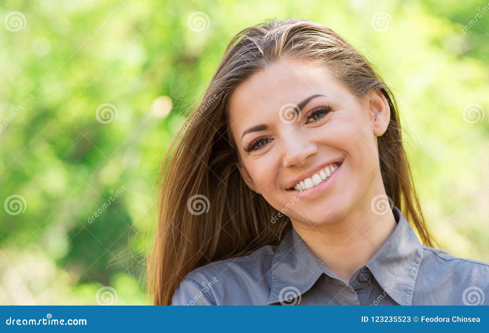 Jeune femme avec du charme souriant dehors