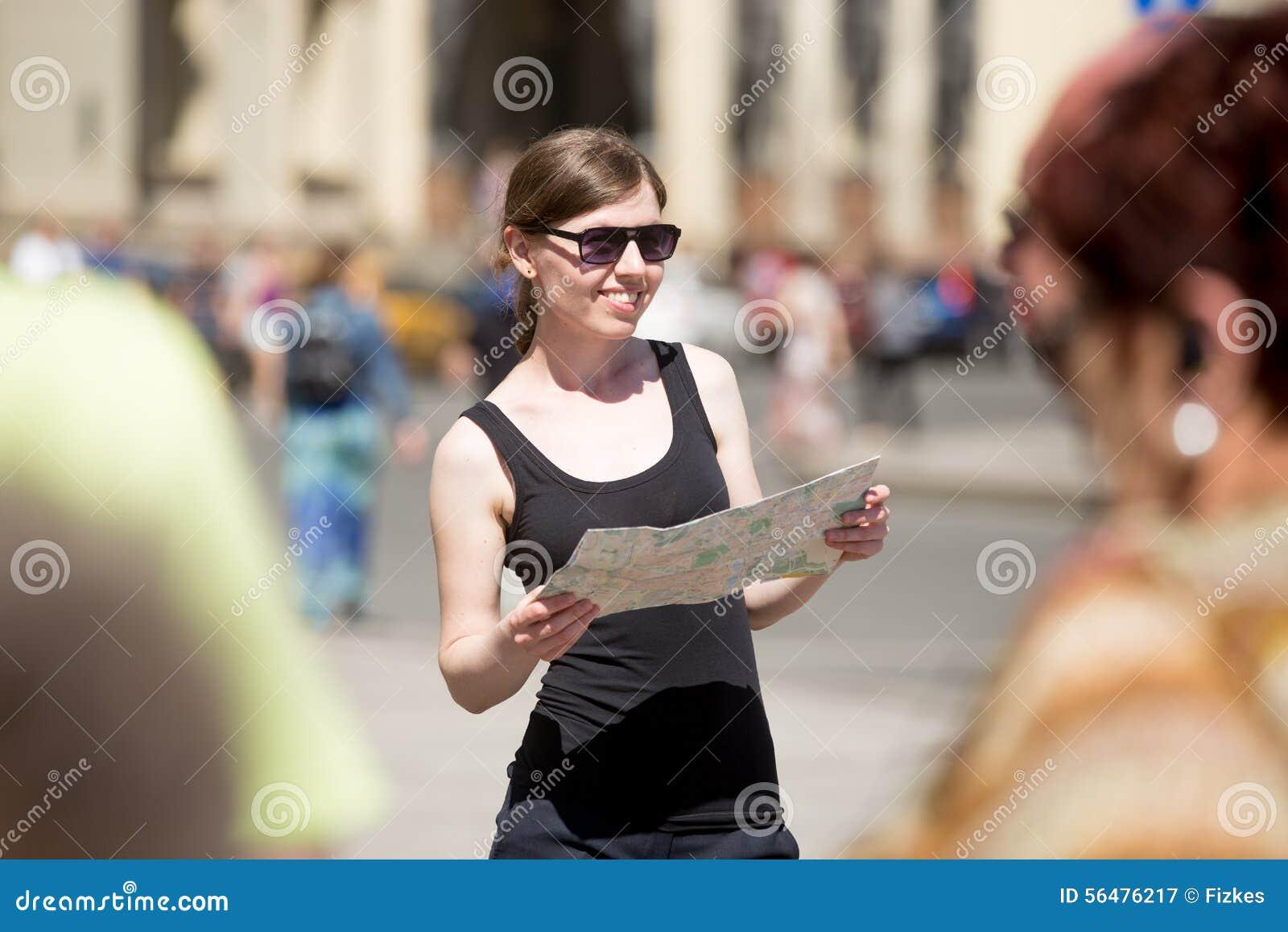 Jeune femme avec la carte sur la place serrée