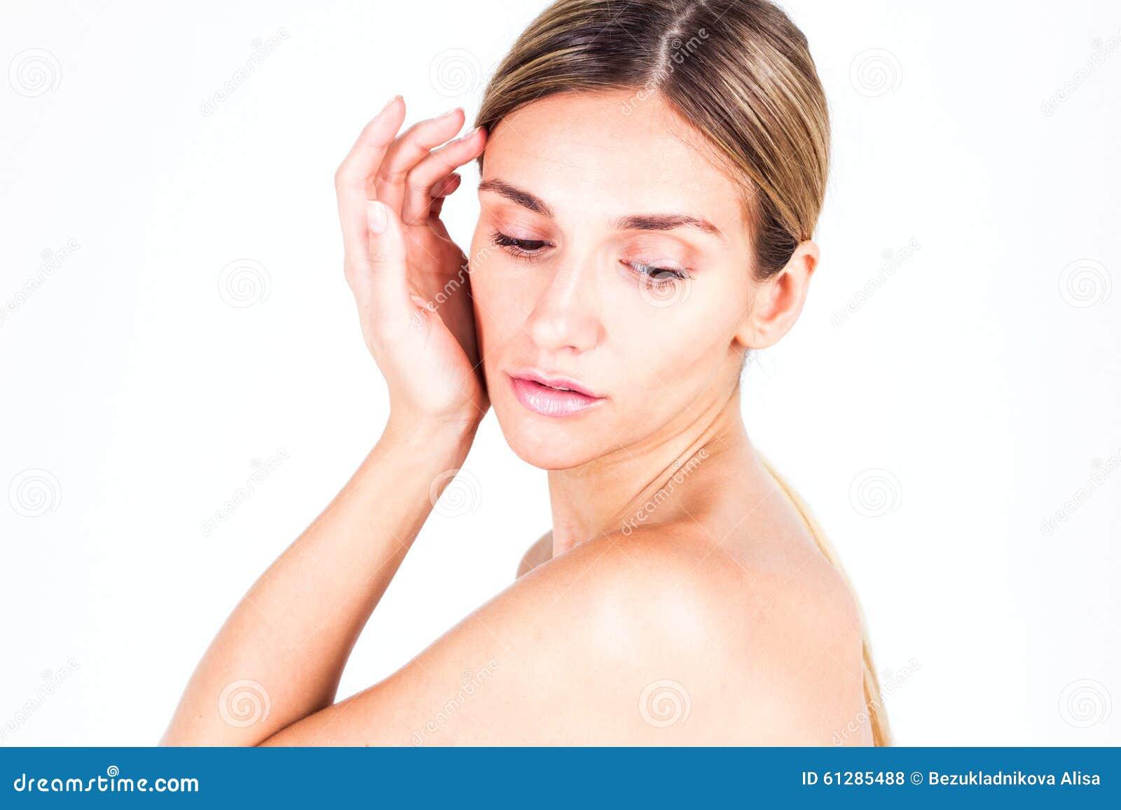 Jeune femme avec la peau lisse tenant sa main près de la joue et regardant vers le bas