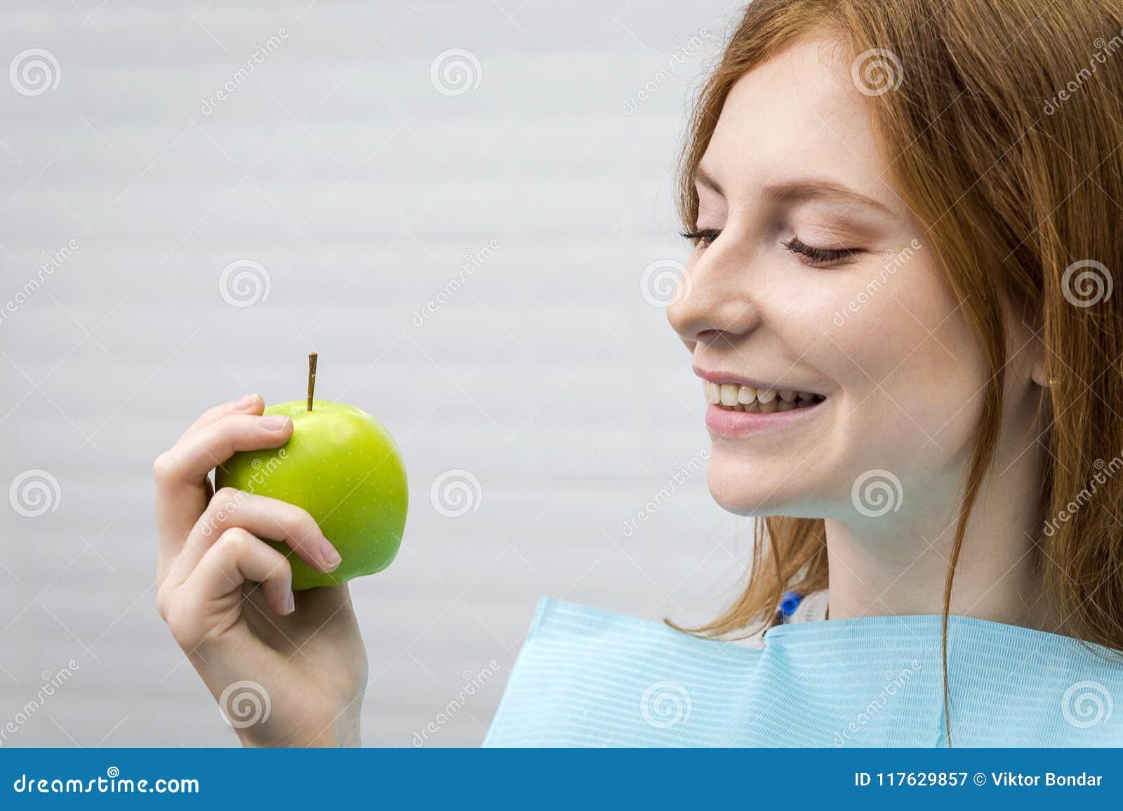 Jeune femme avec la pomme verte acérée de dent saine