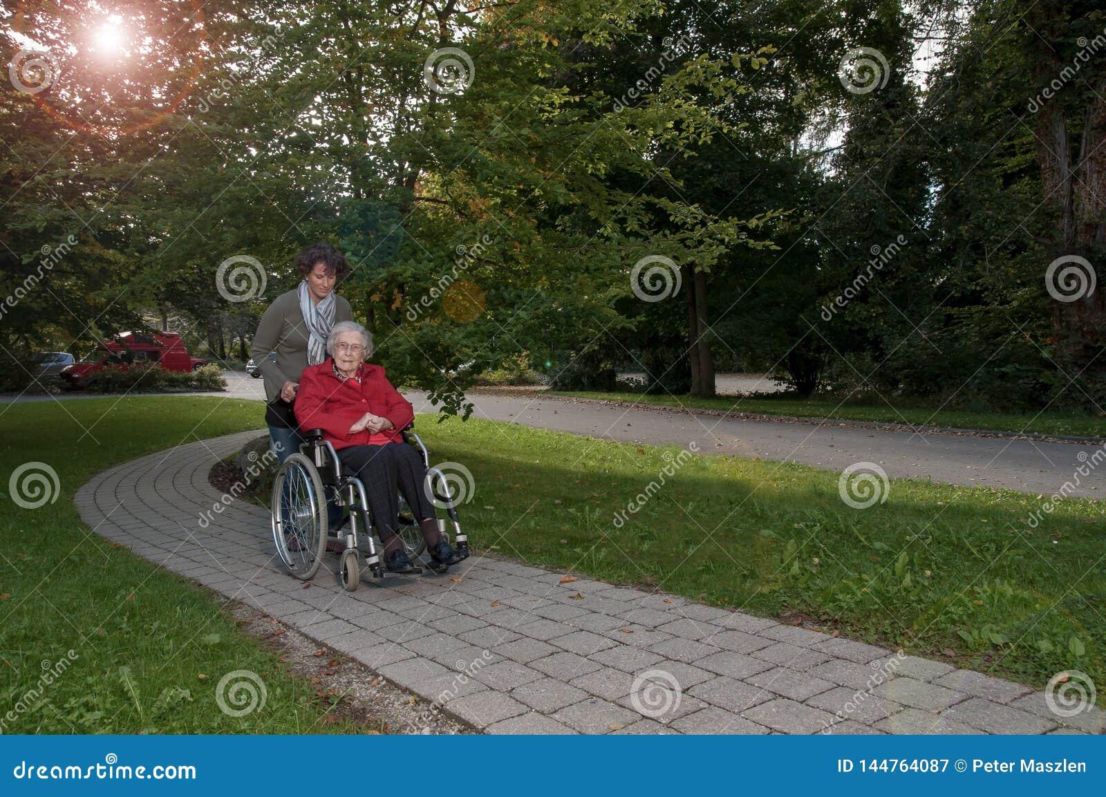 Jeune femme avec la femme supérieure s asseyant dans le fauteuil roulant