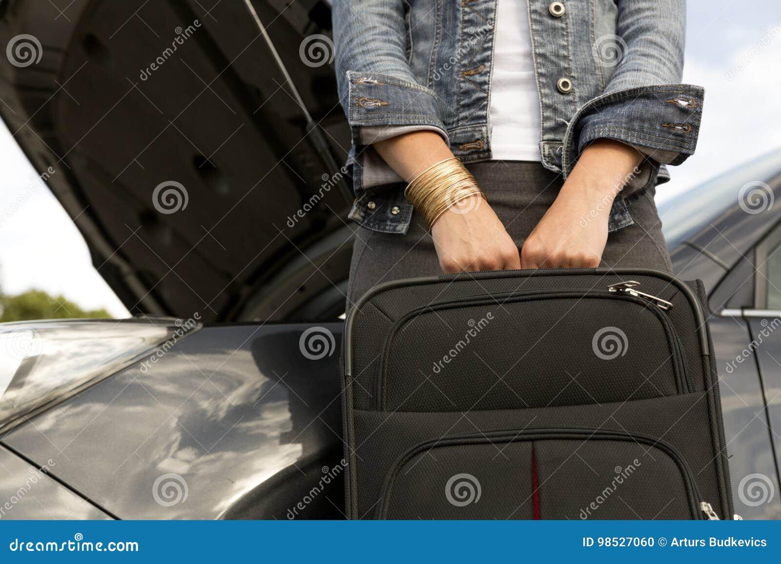 Jeune femme avec la valise à côté de la voiture cassée prête à la laisser