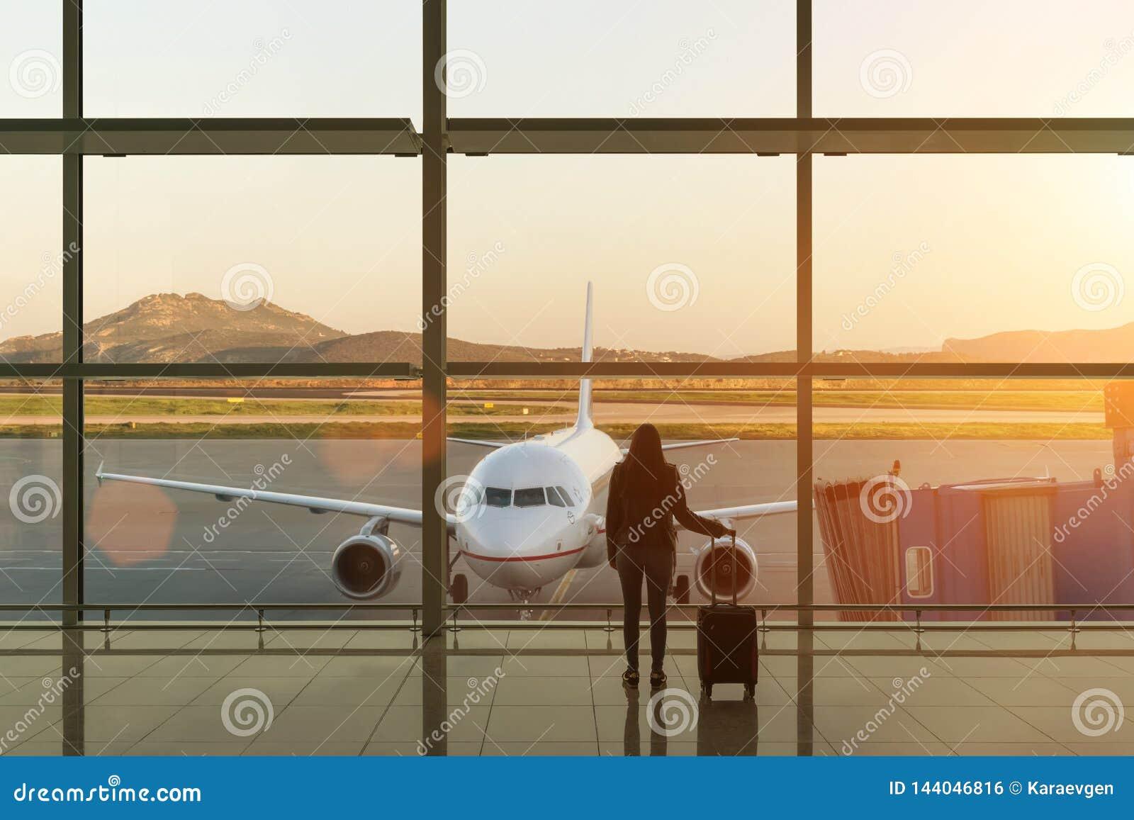 Jeune femme avec la valise dans le hall de départ à l aéroport concept de course