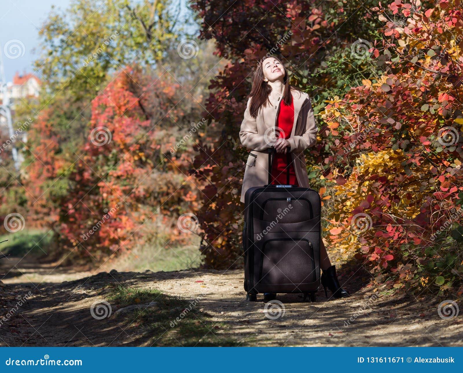 Jeune femme avec la valise de roulement sur la route de campagne dans la forêt
