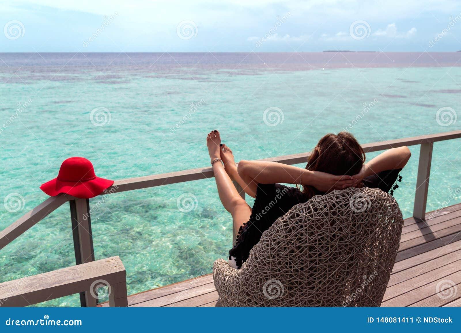 Jeune femme avec le chapeau rouge détendant sur une terrasse et appréciant la liberté dans une destination tropicale