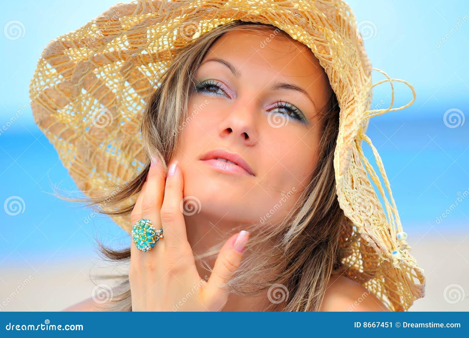 Jeune femme avec le chapeau sur la plage