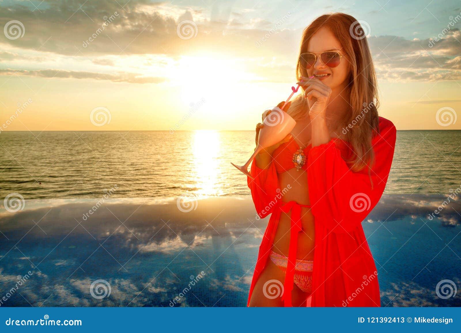 Jeune femme avec le coctail dans la robe d été se tenant sur un fond de piscine et de mer Coucher du soleil