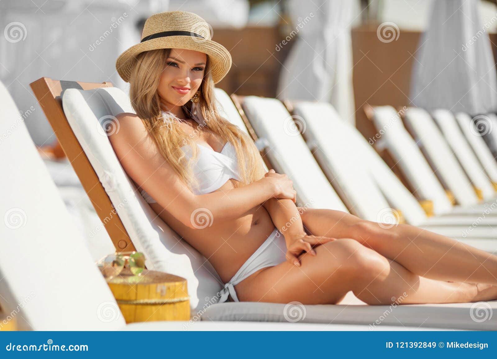 Jeune femme avec le coctail sur la plage à l été