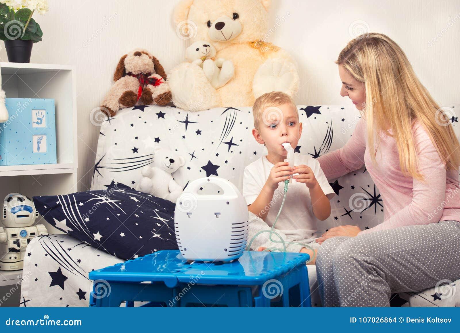 Jeune femme avec le fils faisant l inhalation avec un nébuliseur à la maison