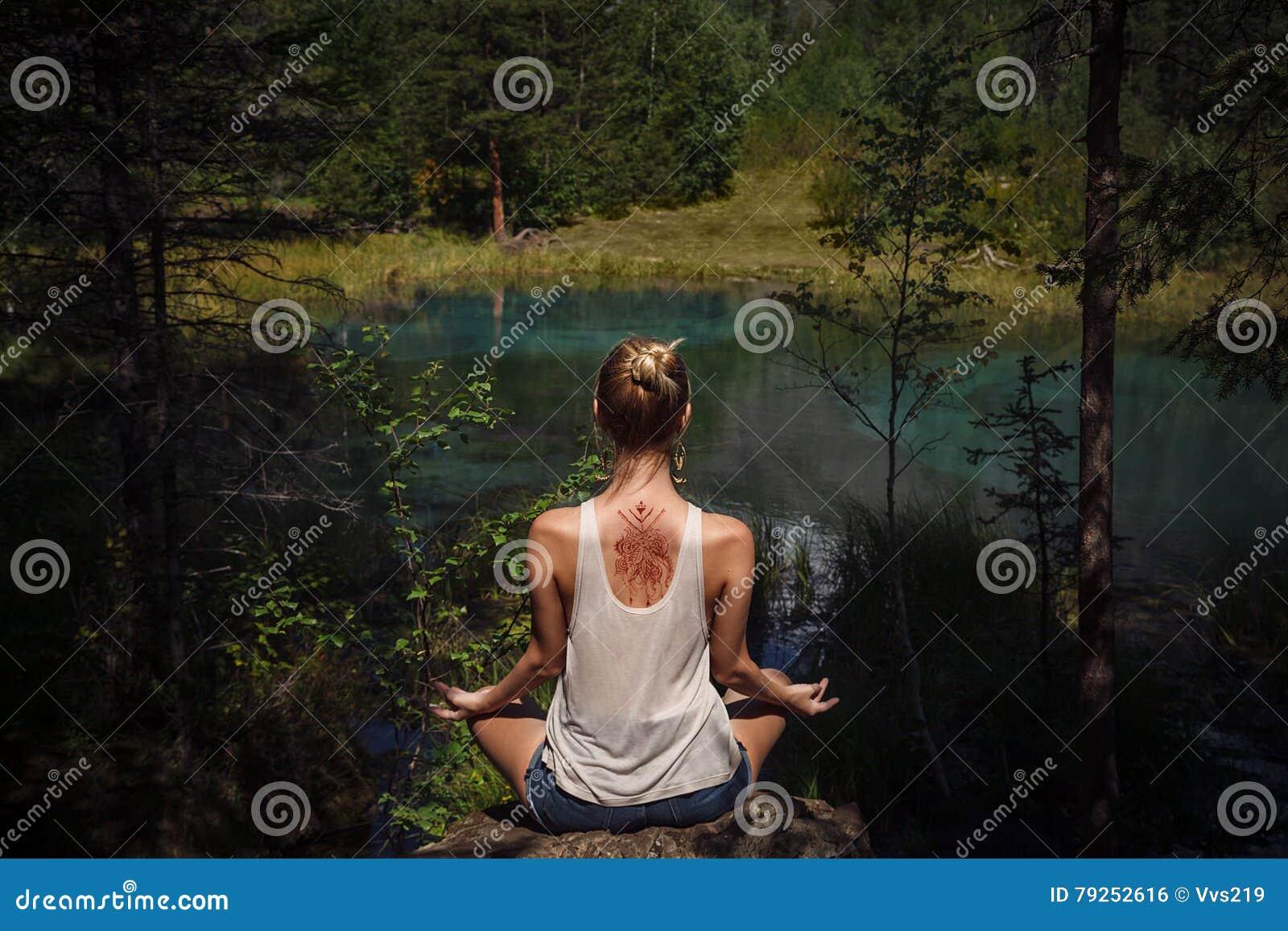 Jeune femme avec le mehendi sur son méditer de retour près du mounta bleu