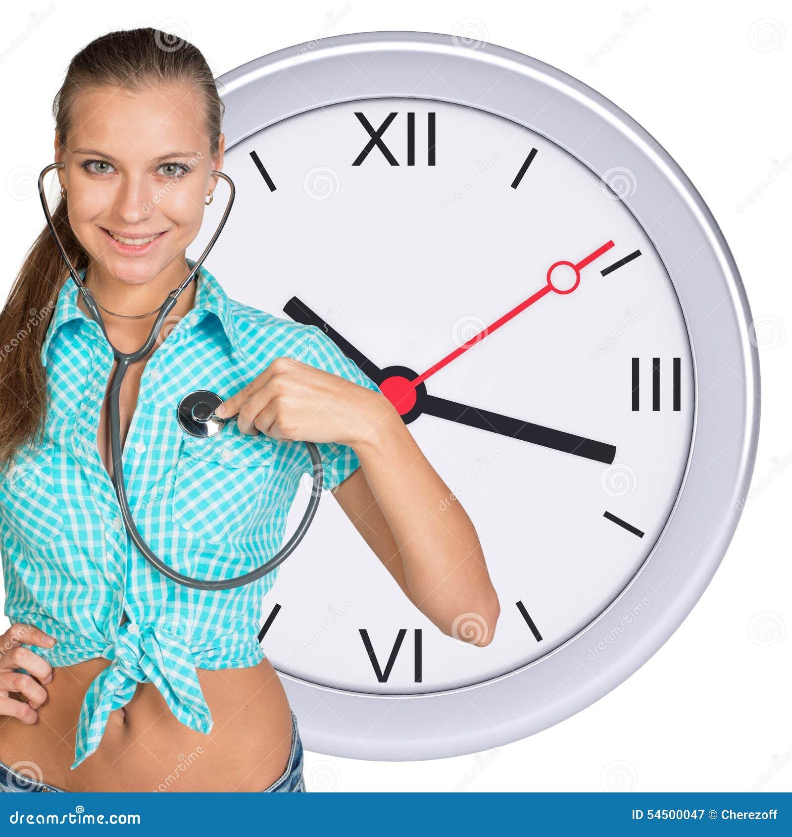 Jeune femme avec le stéthoscope et l horloge