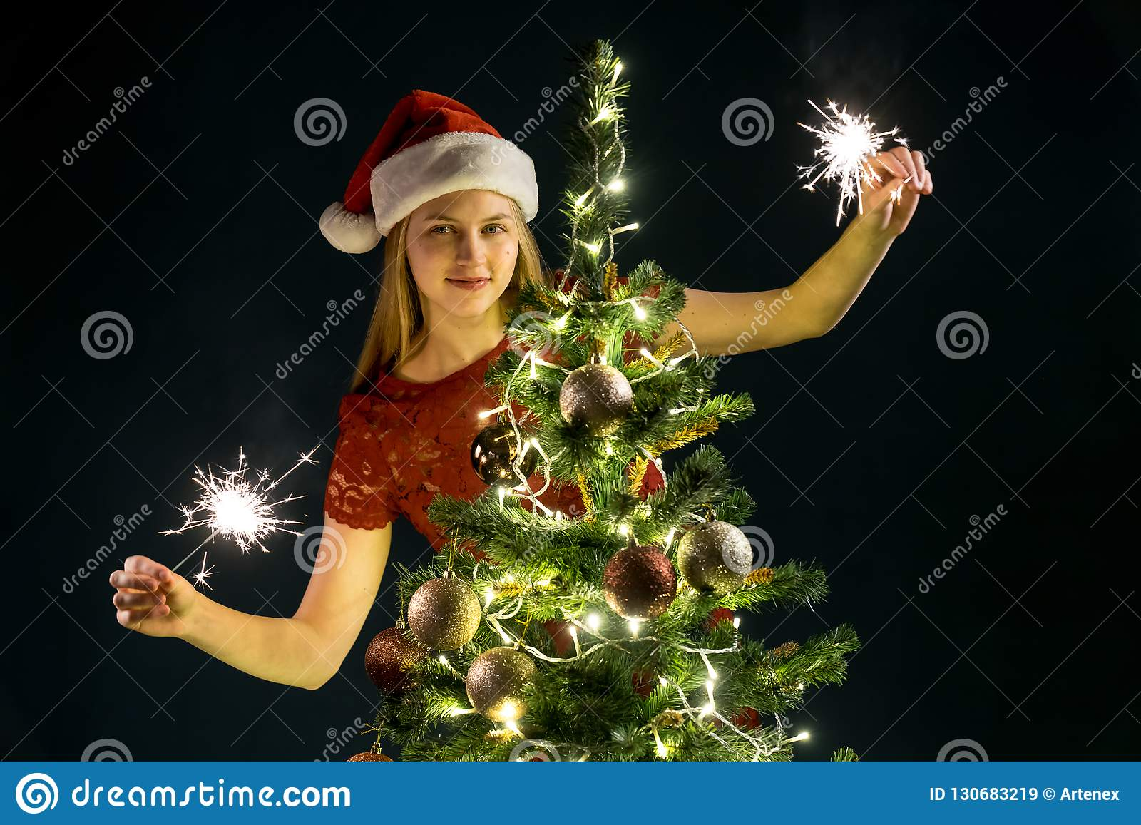 Jeune femme avec les bougies de scintillement, l arbre de Noël et le fond décoratif de bokeh d éclairage Elf et sapin avec des dé
