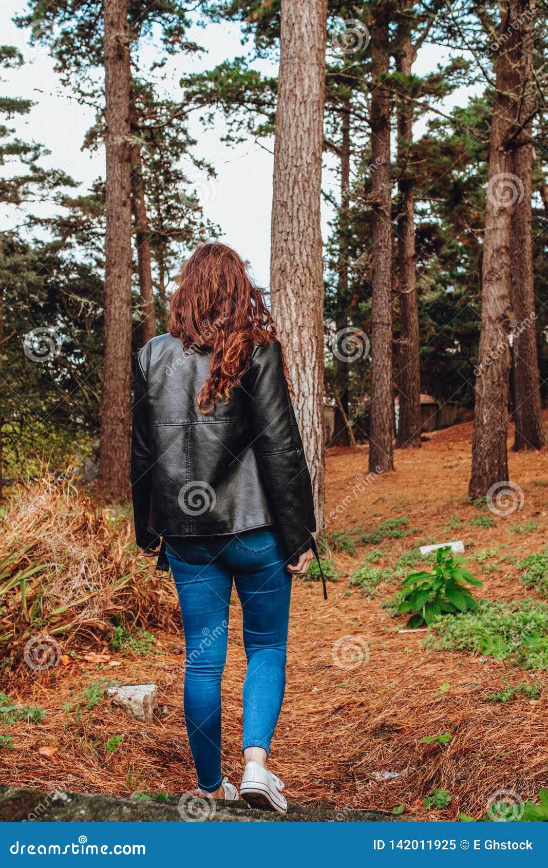 Jeune femme avec les cheveux bouclés et la veste noire marchant par les bois