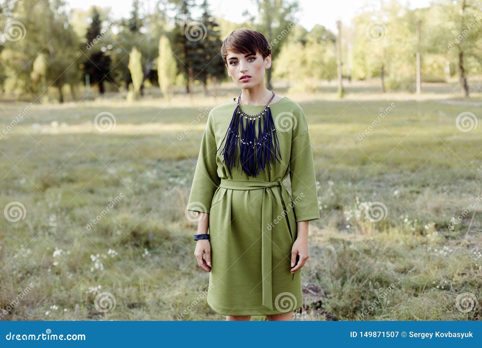 Jeune femme avec les cheveux courts posant dehors