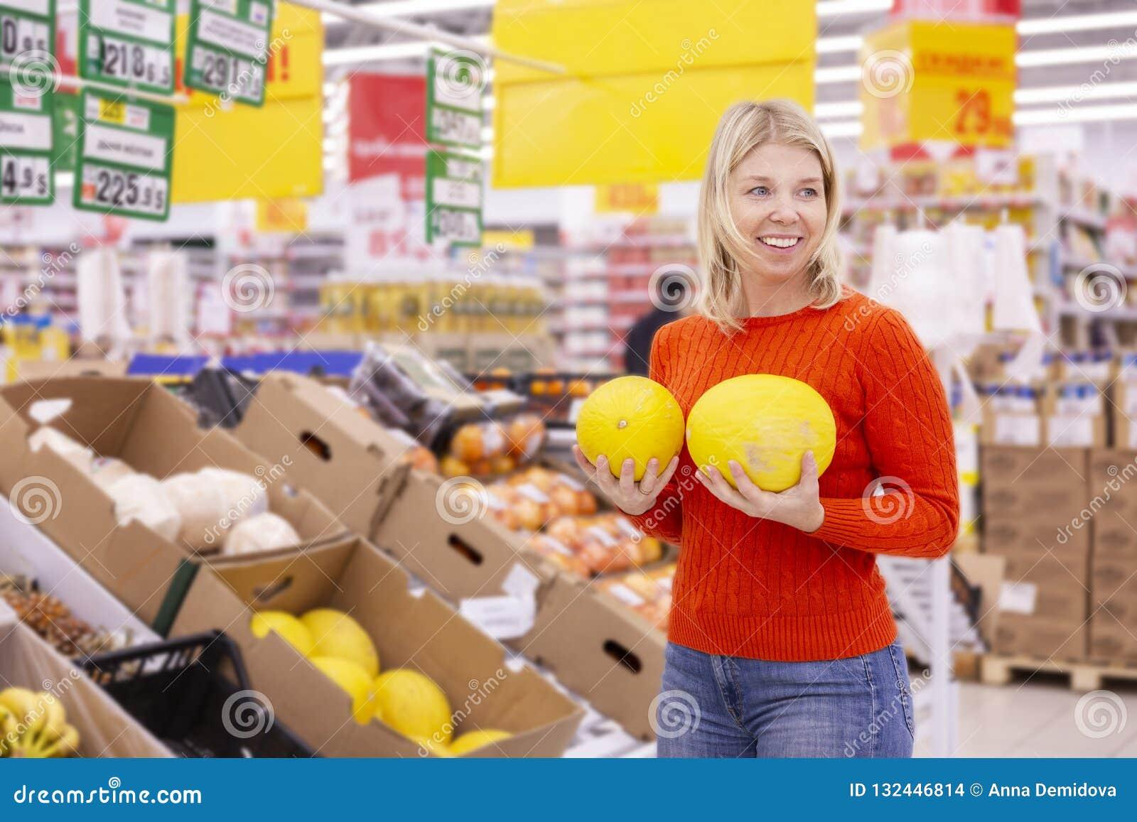 Jeune femme avec les melons juteux dans le supermarché