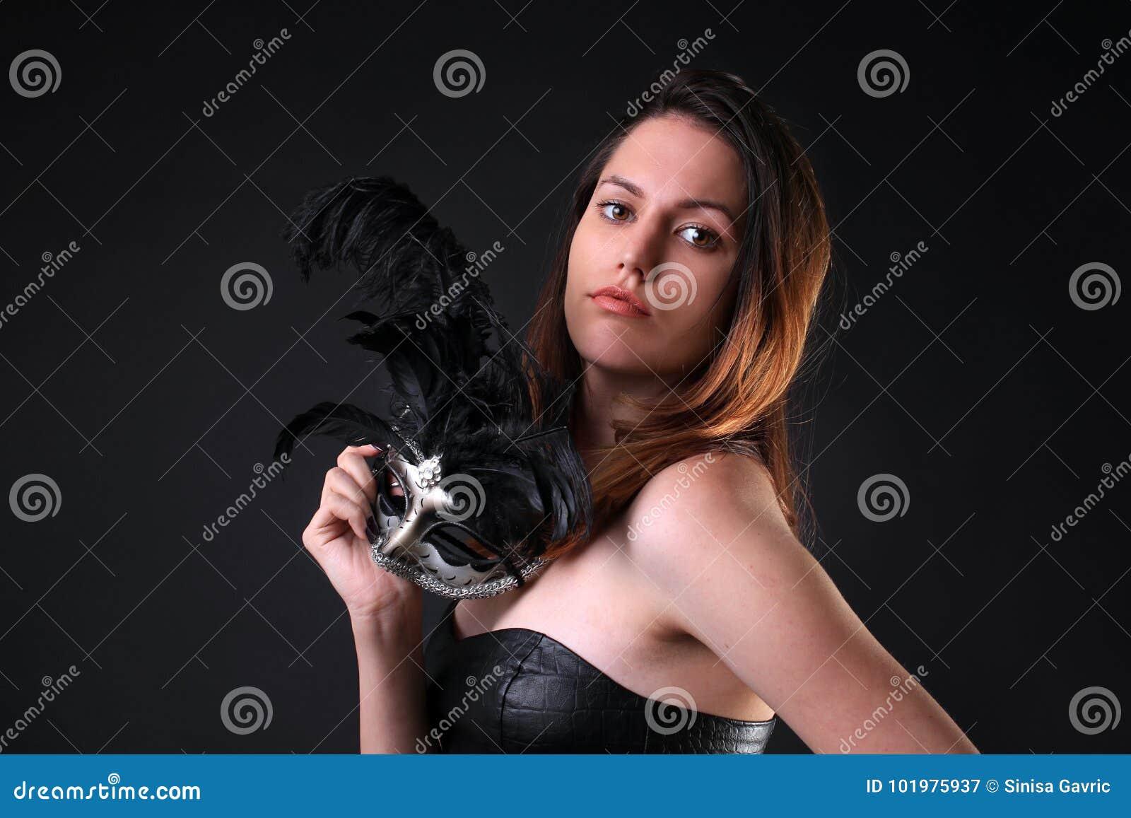 Jeune femme avec un masque argenté noir de carnaval