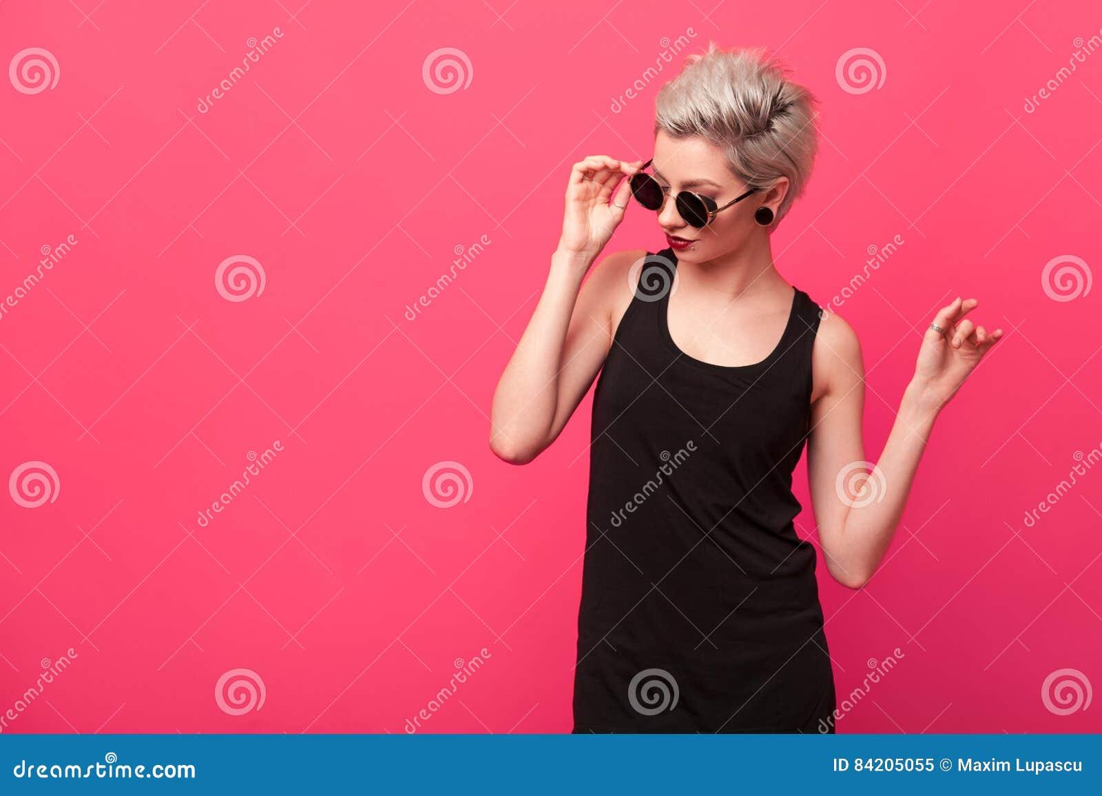 Jeune femme blonde élégante dans rétros lunettes de soleil rondes