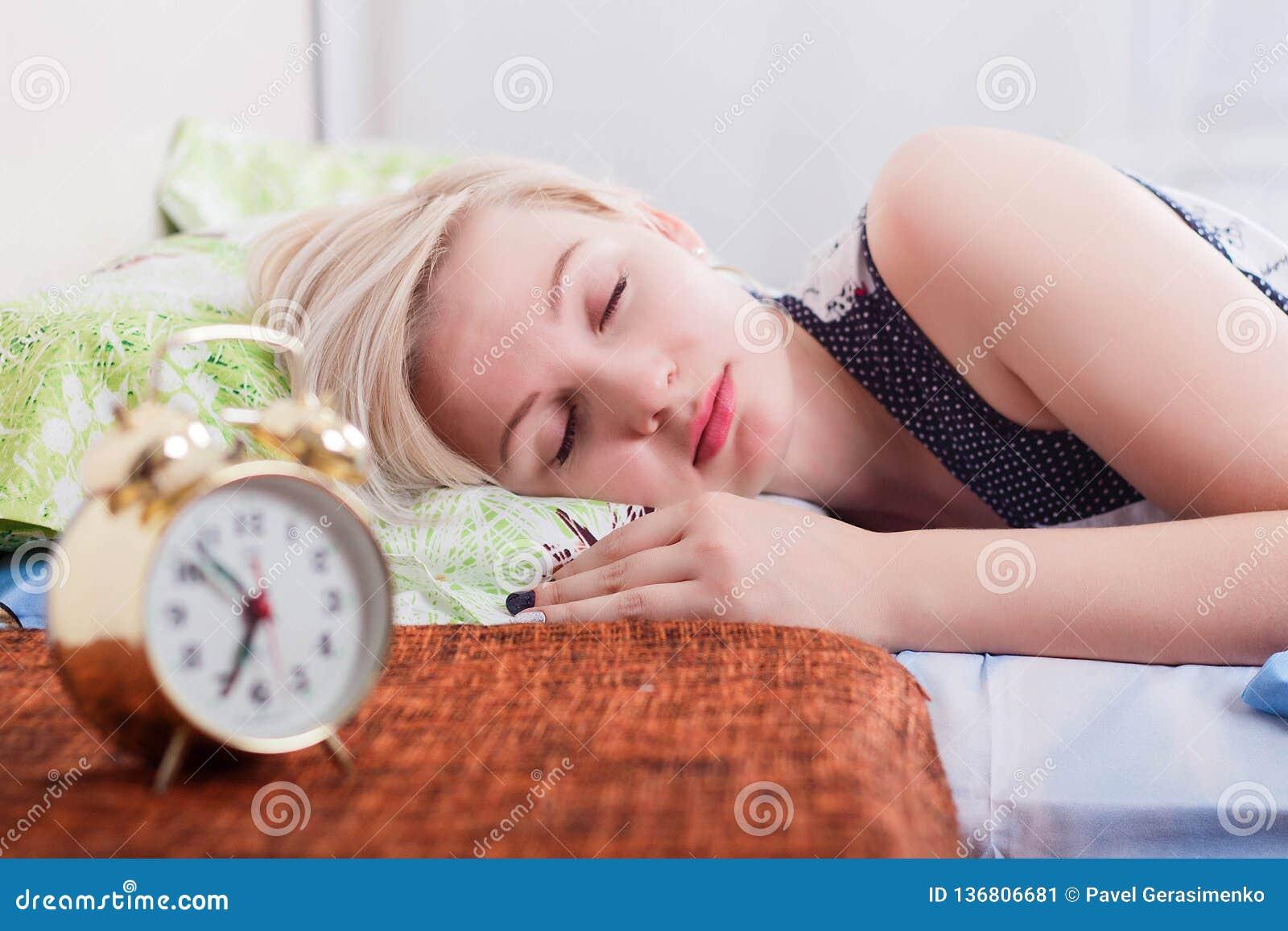 Jeune femme blonde de sommeil dans la chambre à coucher lumineuse à la maison, matin L horloge brouillée dans l avant