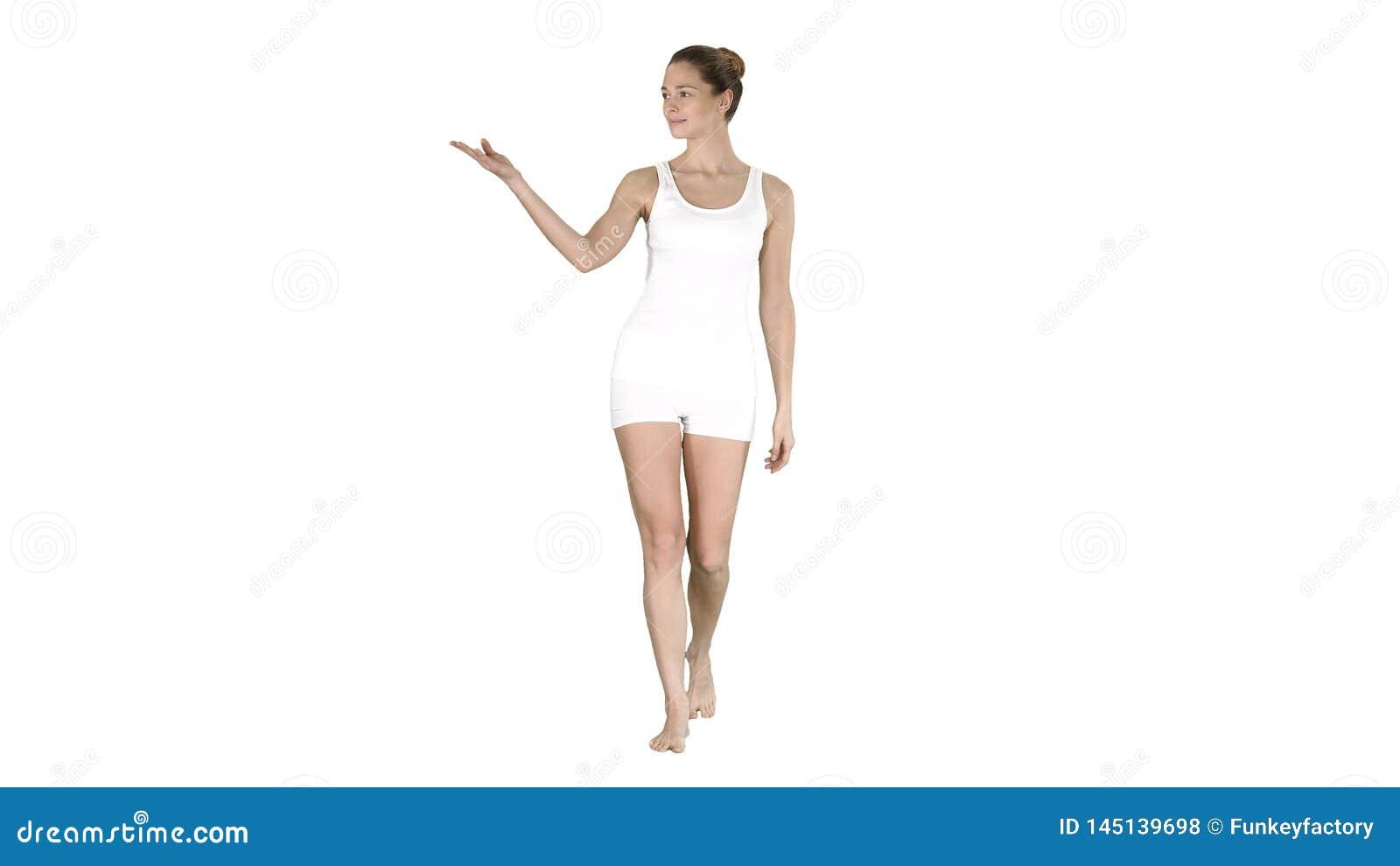 Jeune femme blonde marchant et se dirigeant pour d?grossir montrant sur quelque chose sur le fond blanc
