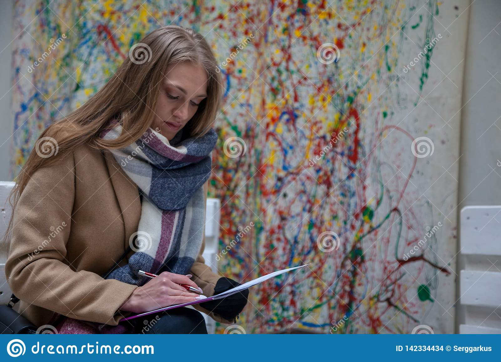 Jeune femme blonde situant sur le banc et l écriture
