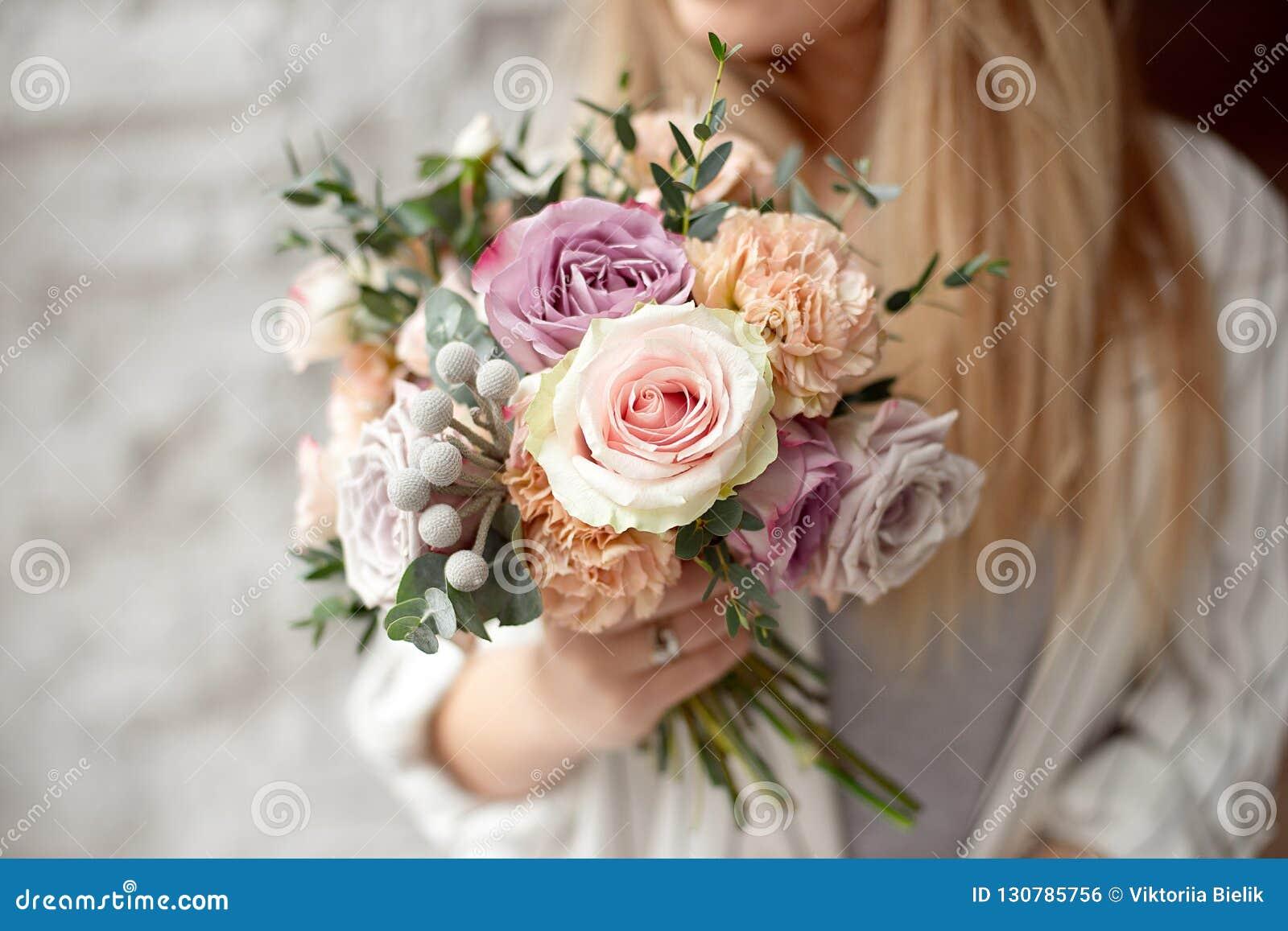 Jeune femme caucasienne en gros plan tenant le bouquet des fleurs, regards par la fenêtre avec le sourire heureux sur le visage s