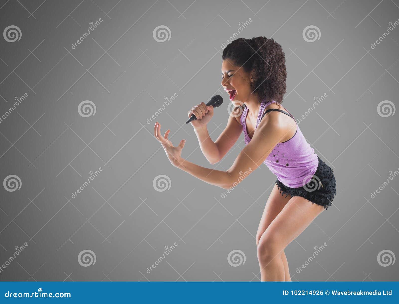 Jeune femme chantant avec le microphone sur le fond gris
