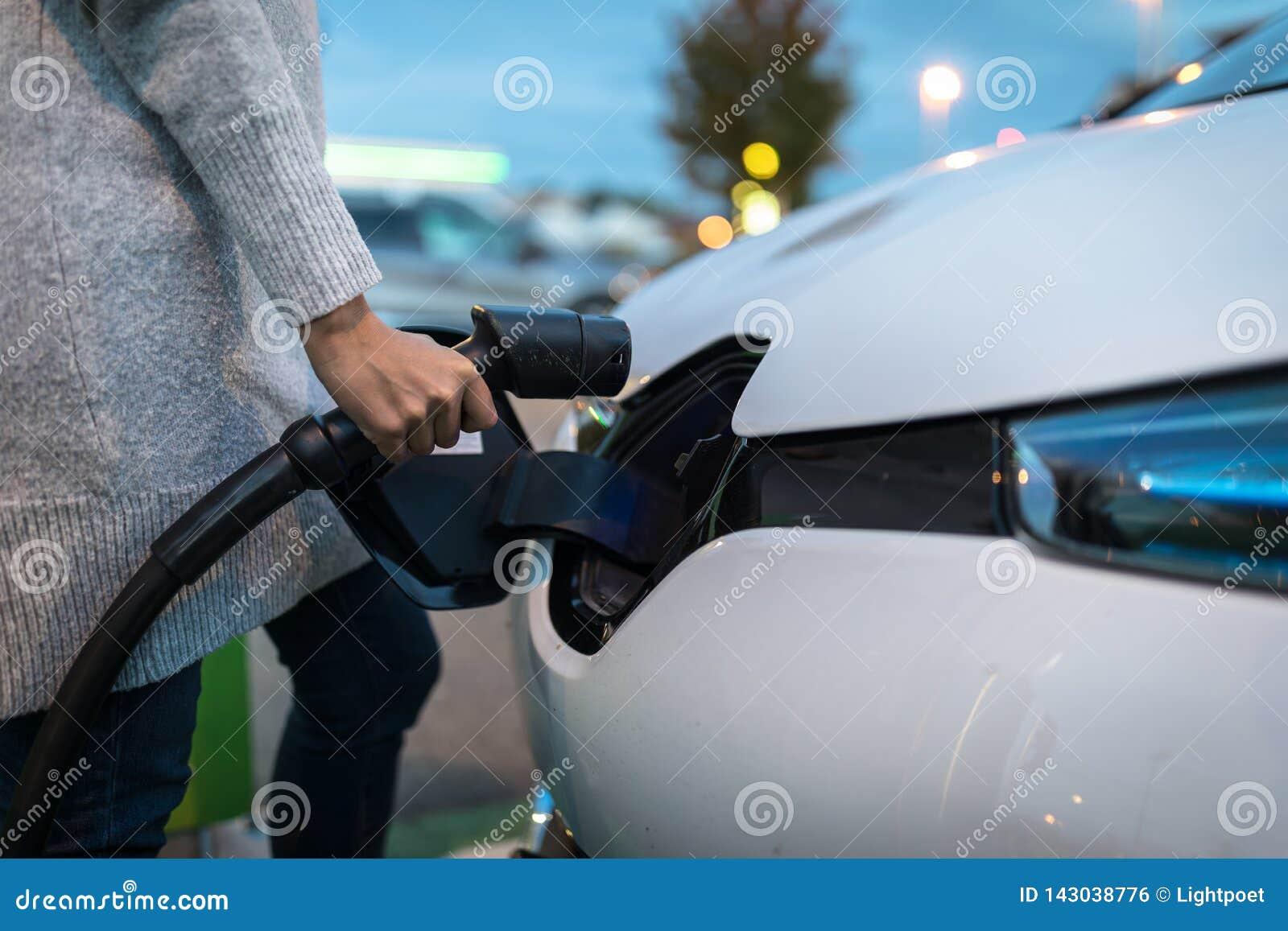 Jeune femme chargeant un véhicule électrique