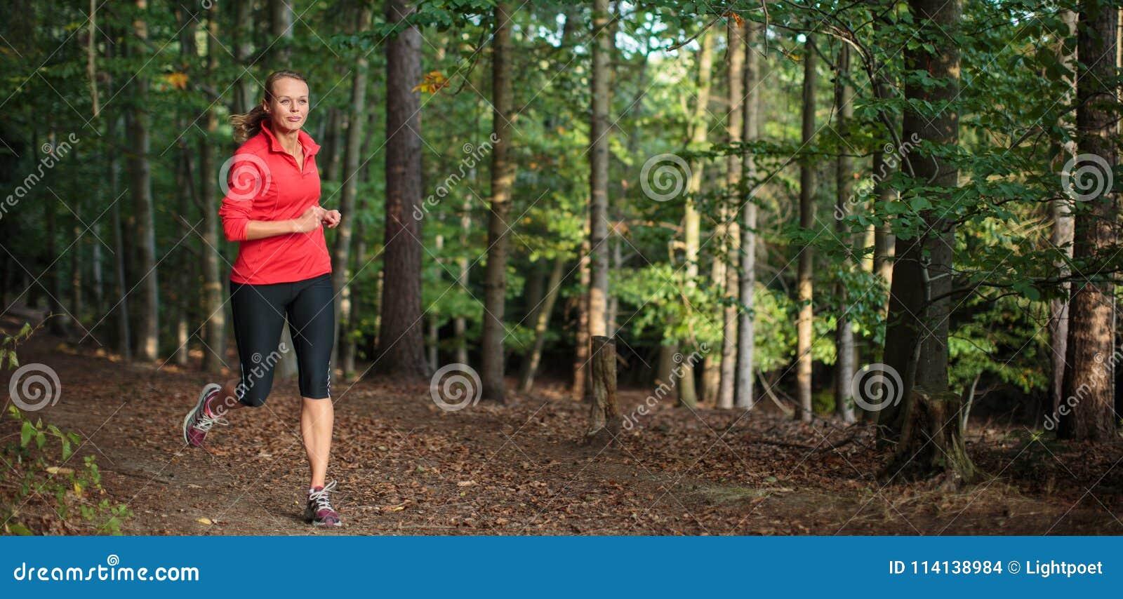 Jeune femme courant dehors dans une forêt