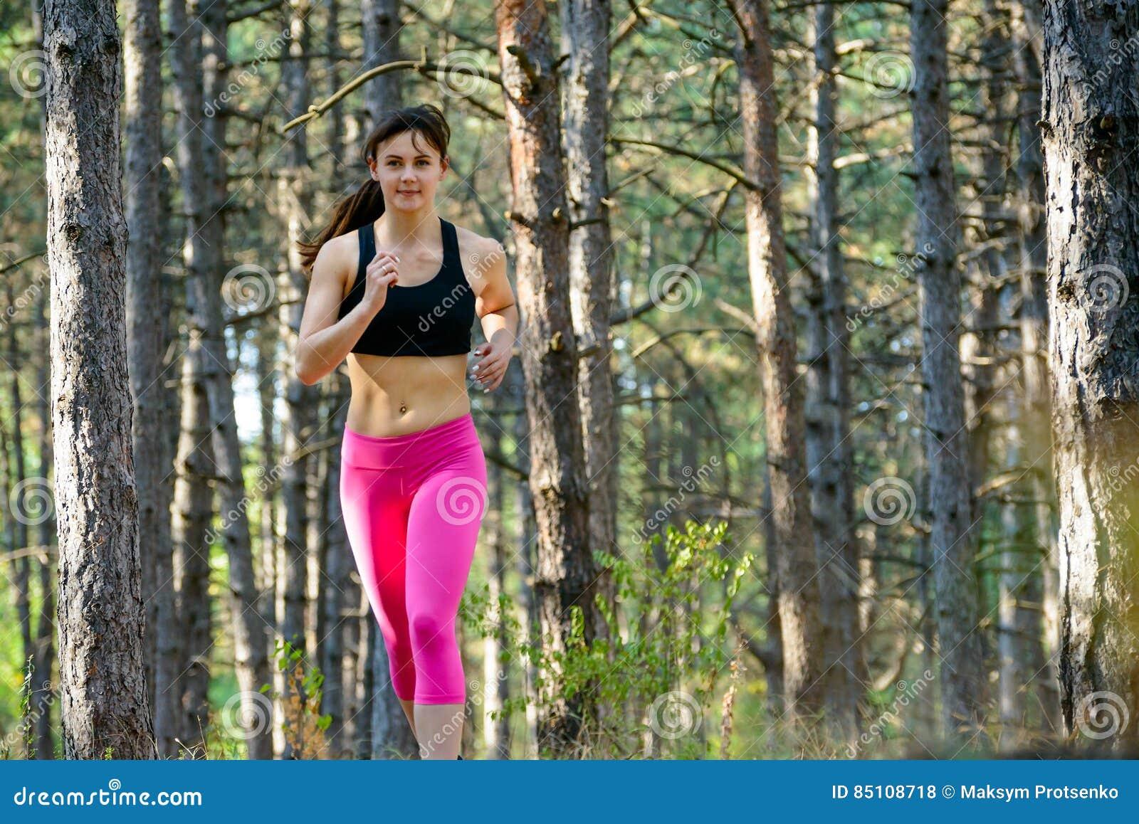 Jeune femme courant sur la traînée dans le beau pin sauvage Forest Active Lifestyle Concept L espace pour le texte
