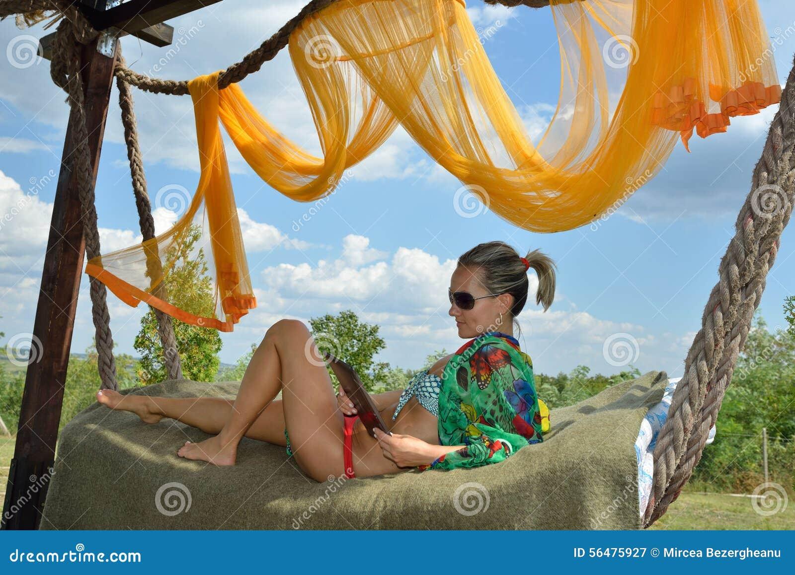 Jeune femme détendant dans l hamac avec le comprimé