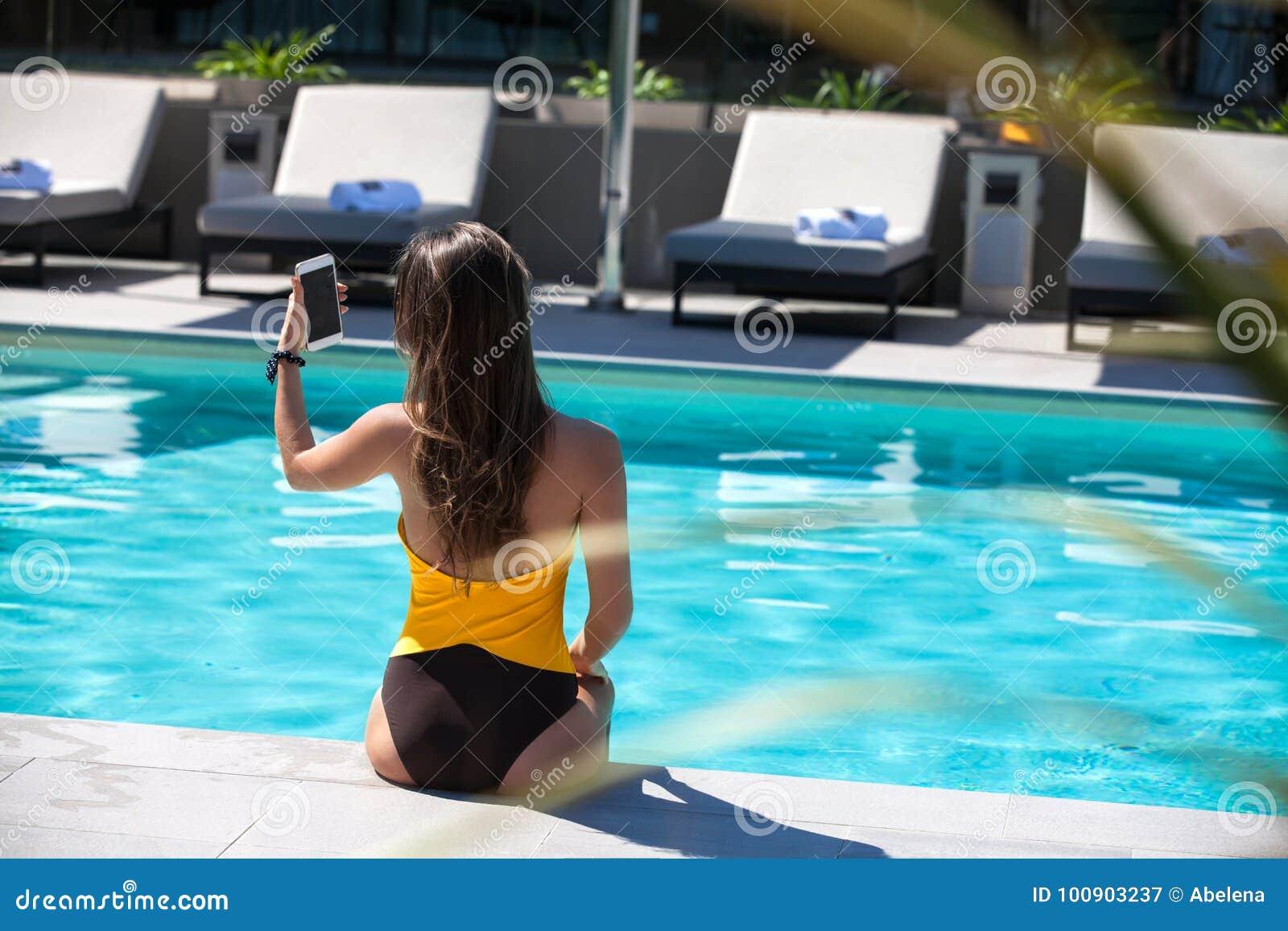 Jeune femme détendant par la piscine