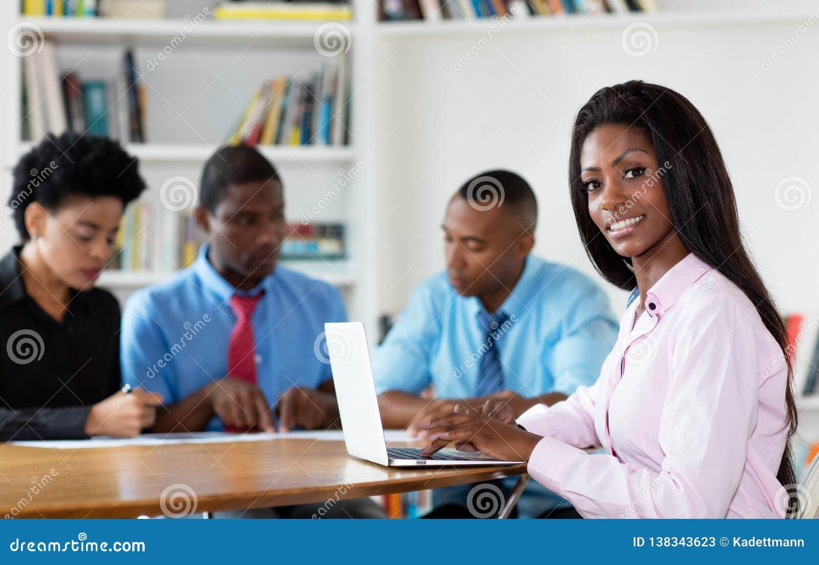 Jeune femme d affaires d afro-américain avec l équipe et l ordinateur