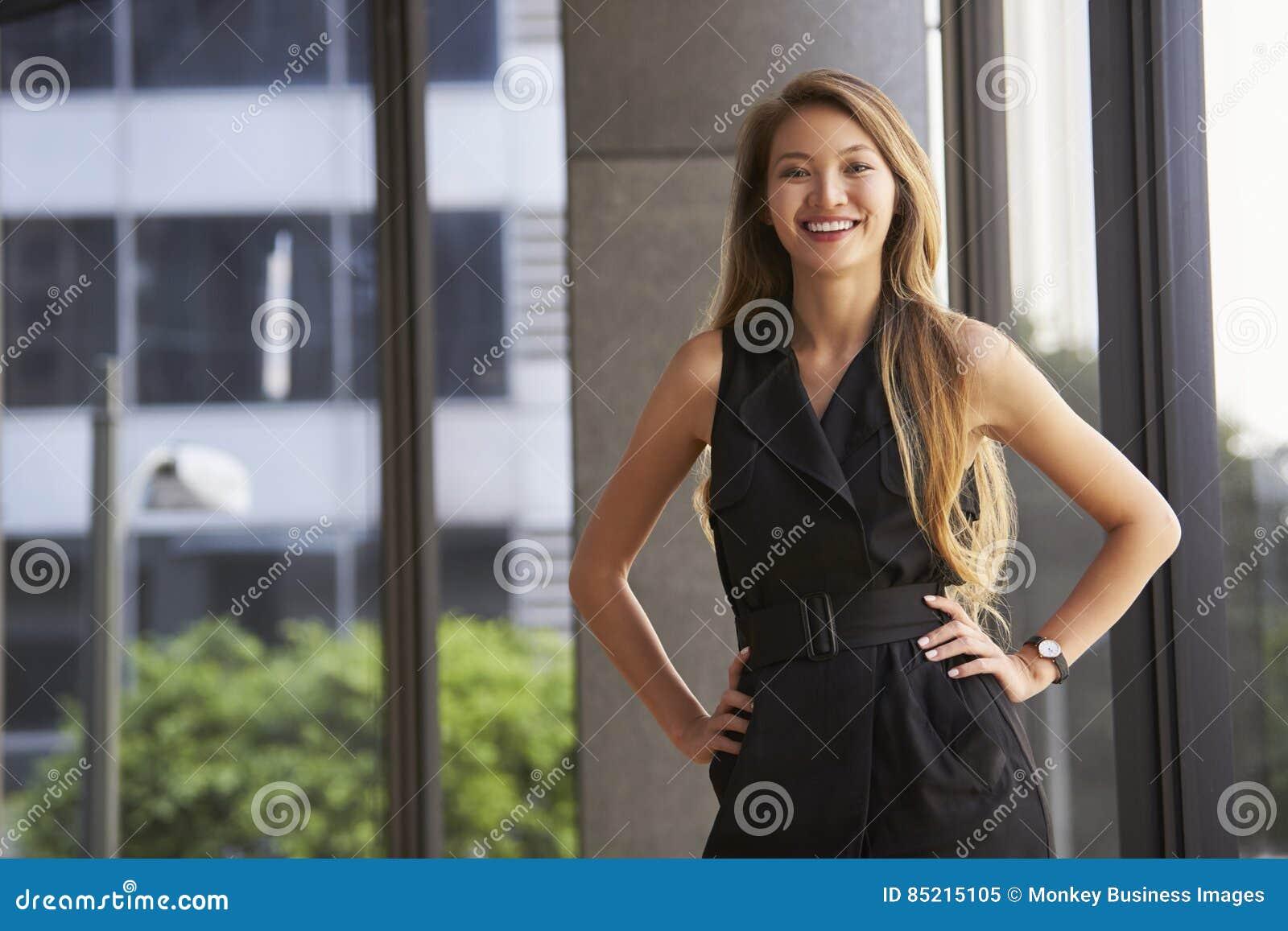 Jeune femme d affaires asiatique regardant à l appareil-photo, mains sur des hanches