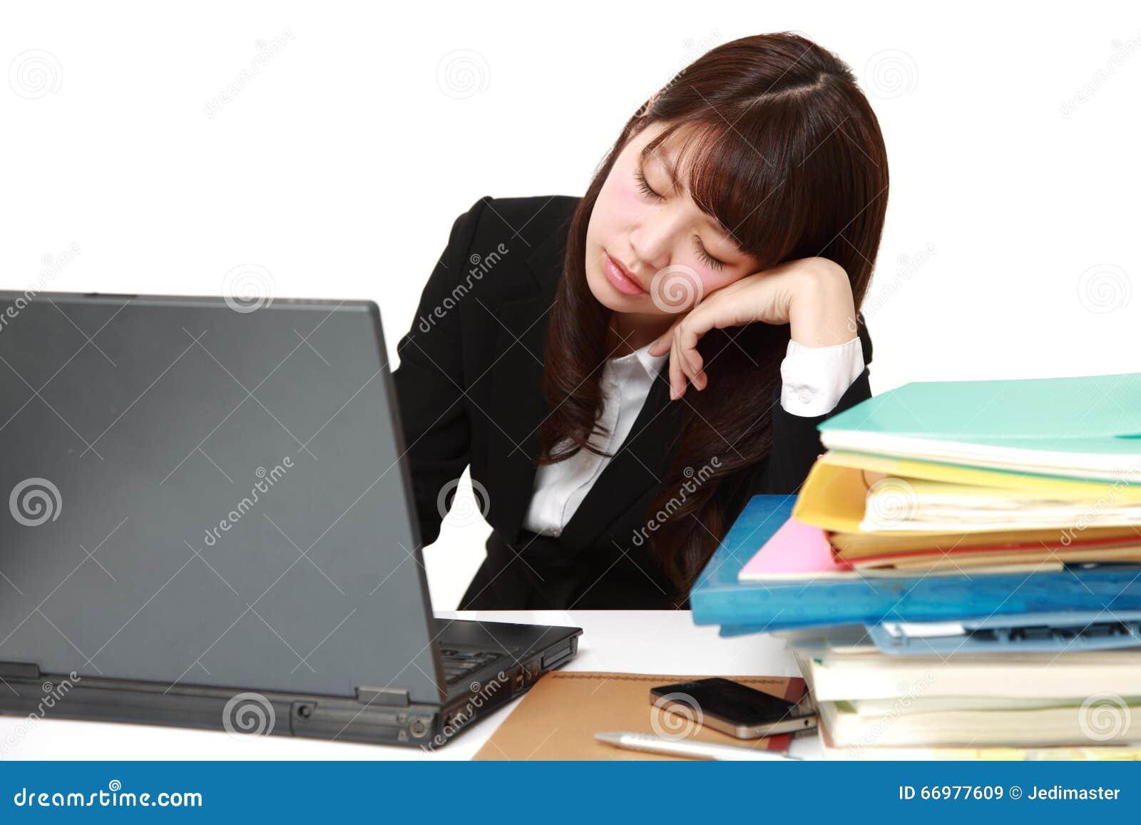 Jeune femme daffaires japonaise dormant sur le bureau image stock