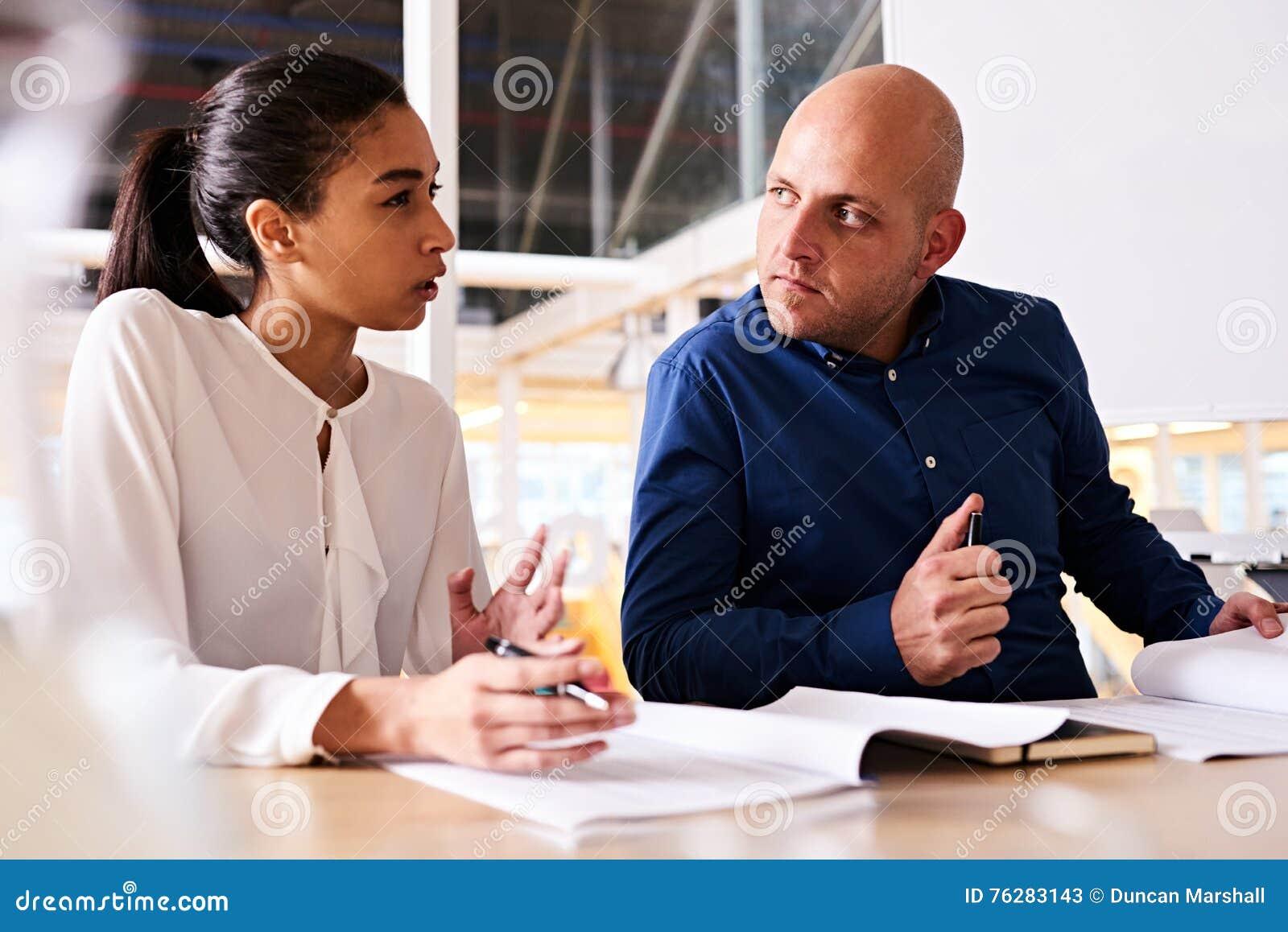 Jeune femme d affaires montrant l incertitude à son associé masculin