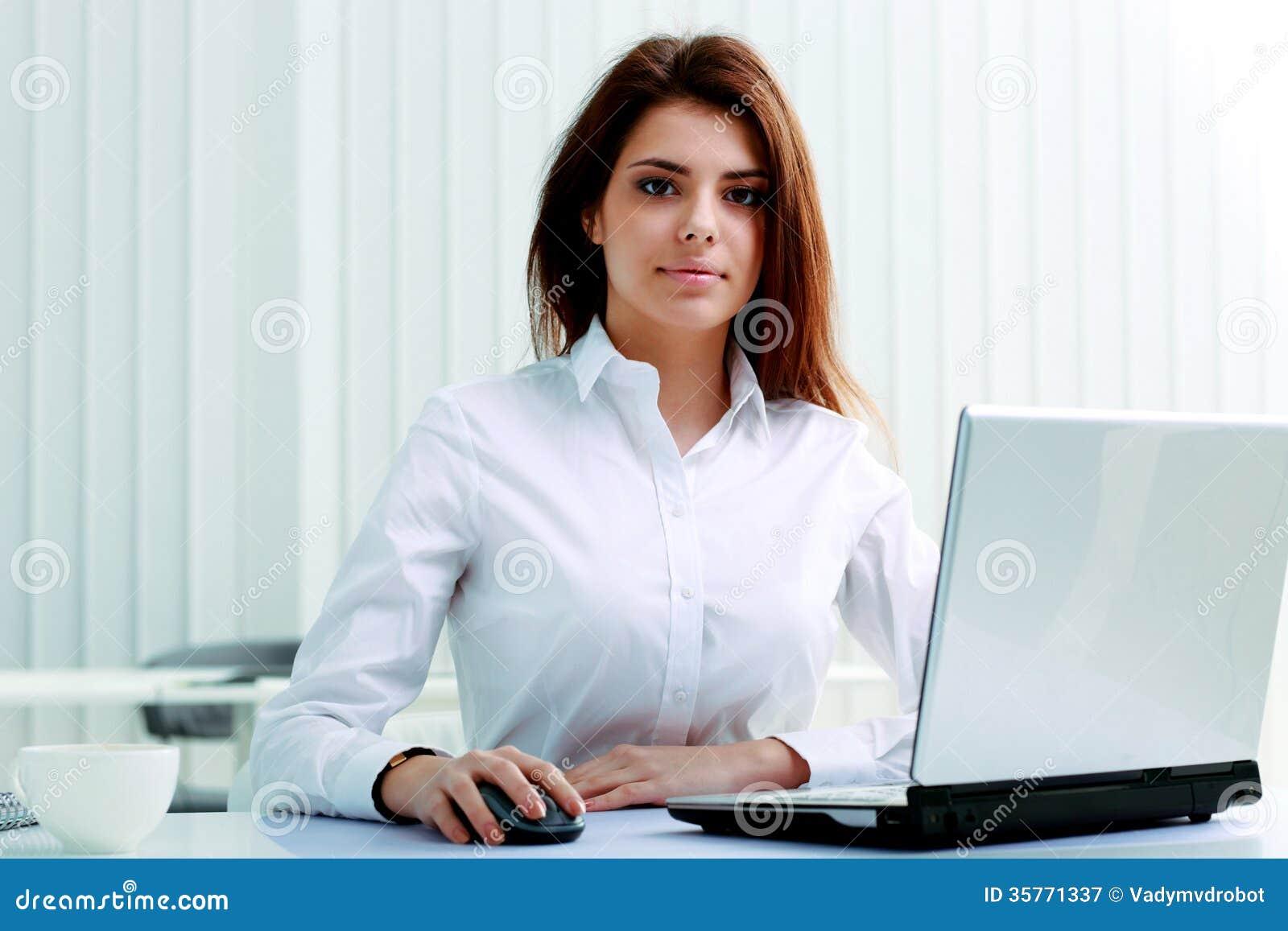 jeune femme d 39 affaires s rieuse s 39 asseyant la table avec l 39 ordinateur portable photographie. Black Bedroom Furniture Sets. Home Design Ideas