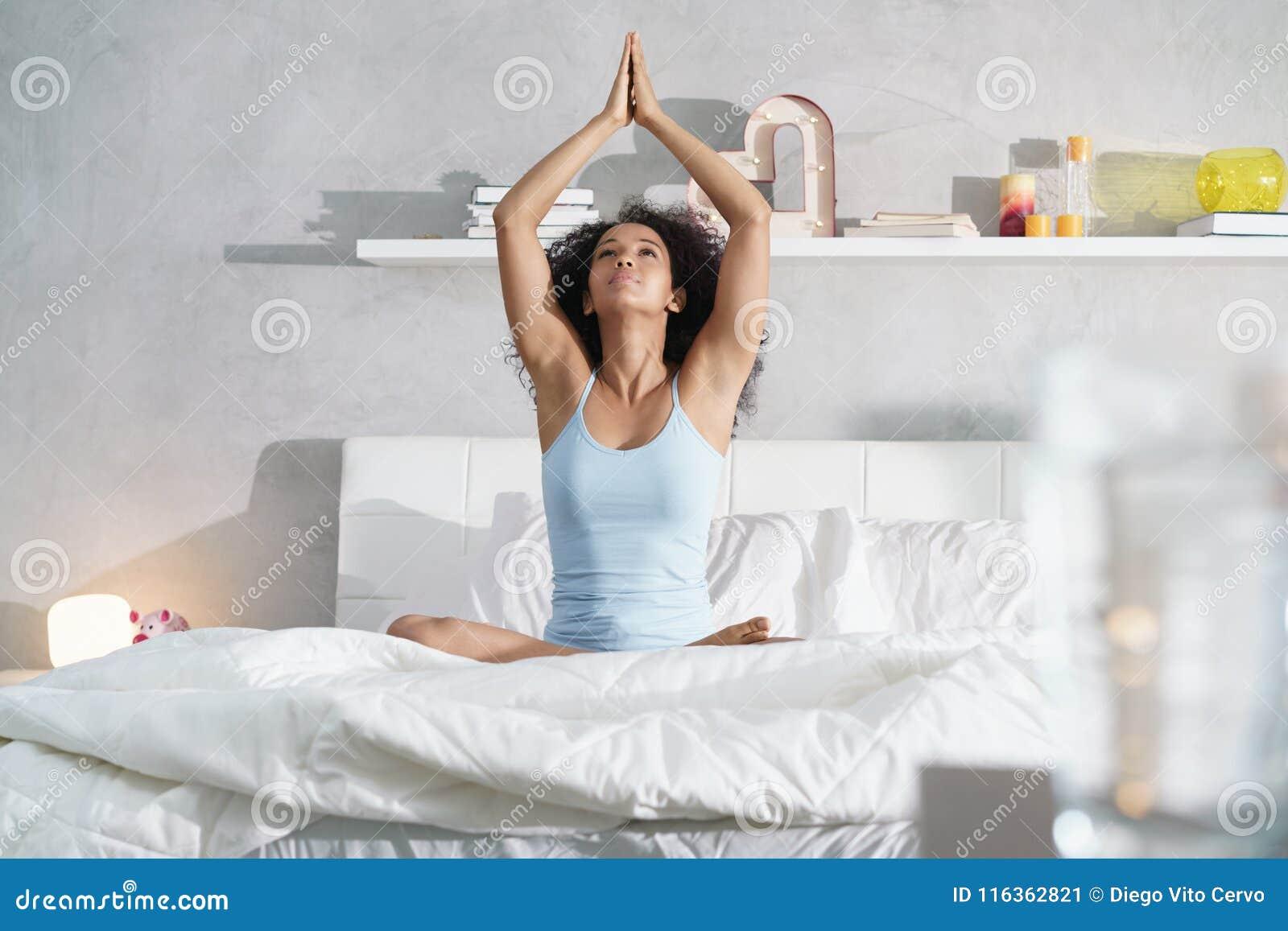 Jeune femme d Afro-américain faisant le yoga dans le lit après sommeil