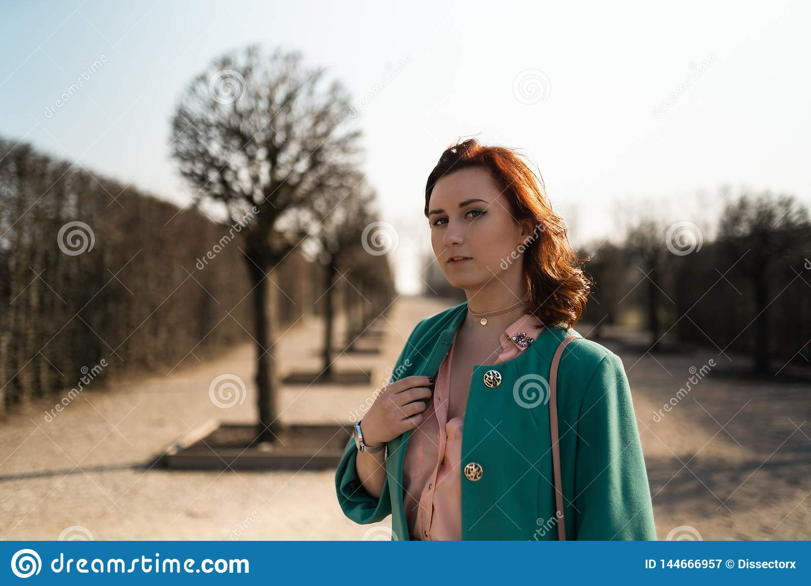 Jeune femme d amant de mode waling en parc utilisant la veste verte vive et une jupe colorée