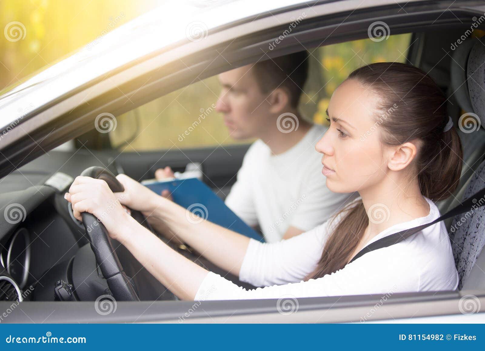 jeune femme d 39 examen de conduite conduisant une voiture homme s 39 asseyant de c t photo stock. Black Bedroom Furniture Sets. Home Design Ideas