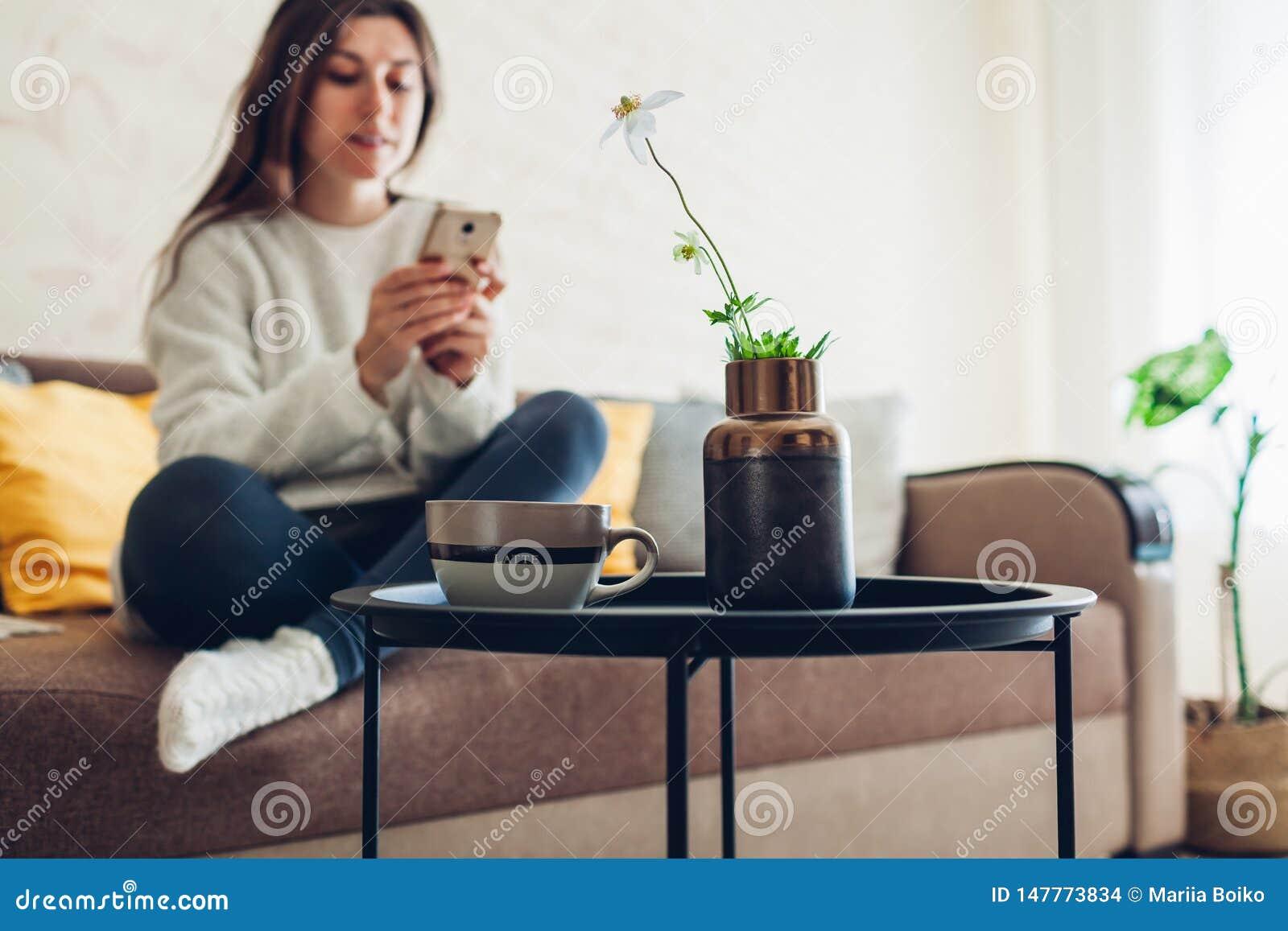 Jeune femme d?tendant dans le salon utilisant le smartphone et le caf? potable D?cor int?rieur
