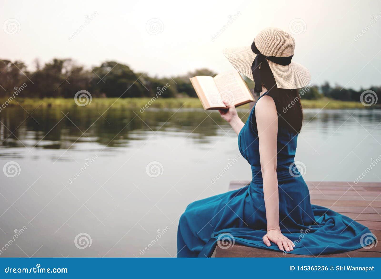 Jeune femme d?tendant par la rive Se reposer sur la plate-forme et le livre de lecture