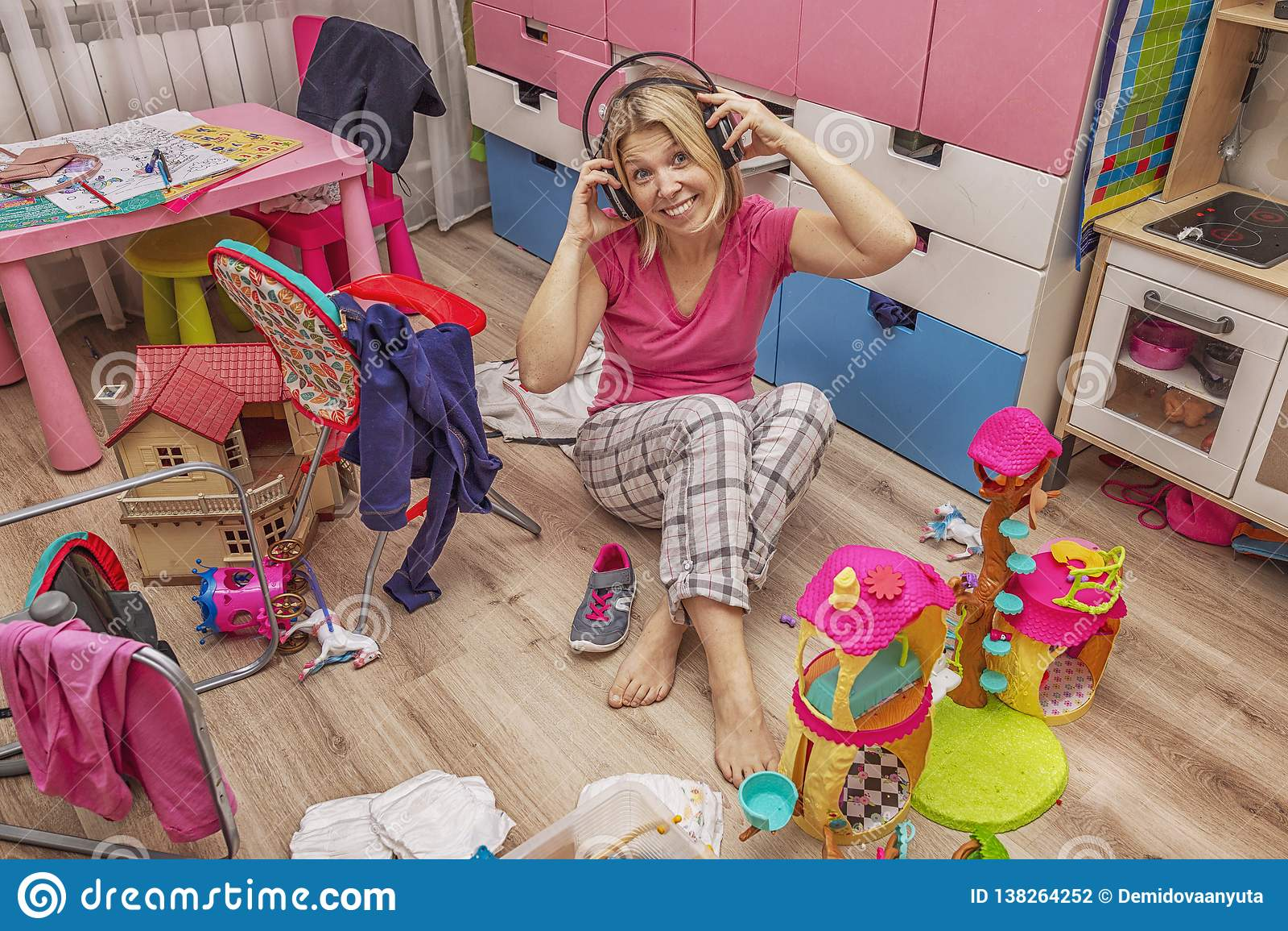 Jeune femme dans des écouteurs dans une salle de désordre