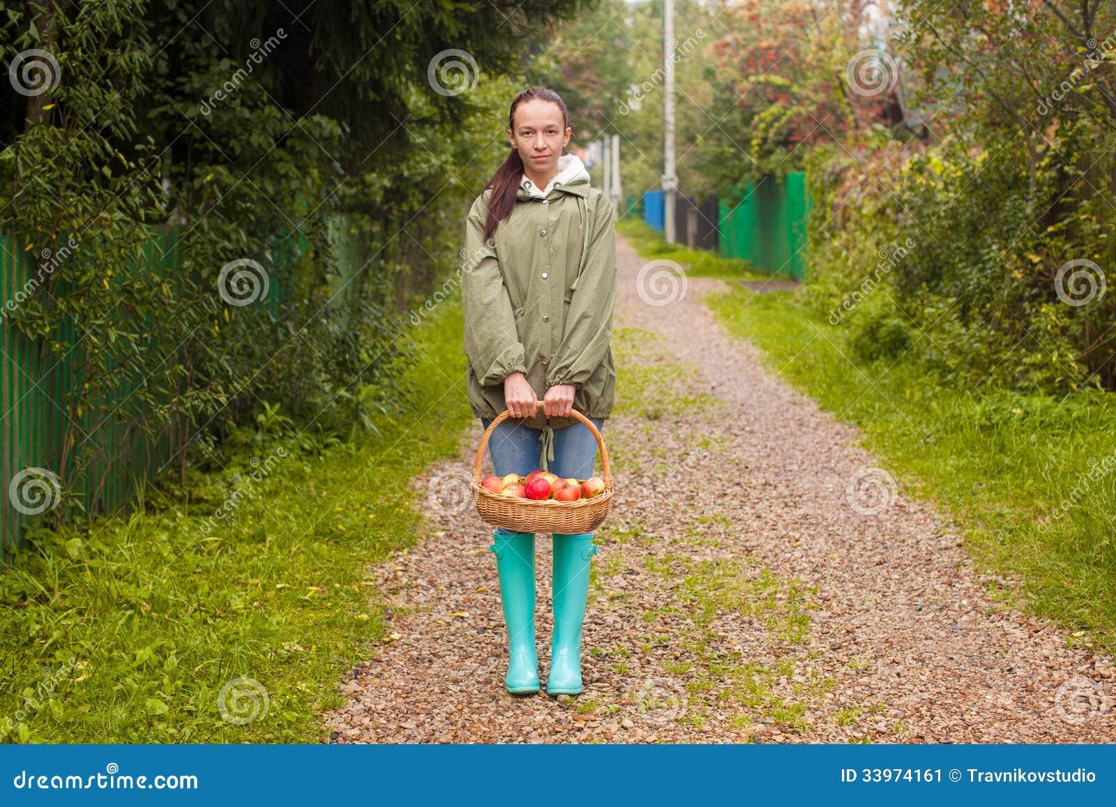 jeune femme dans des bottes en caoutchouc avec le panier. Black Bedroom Furniture Sets. Home Design Ideas